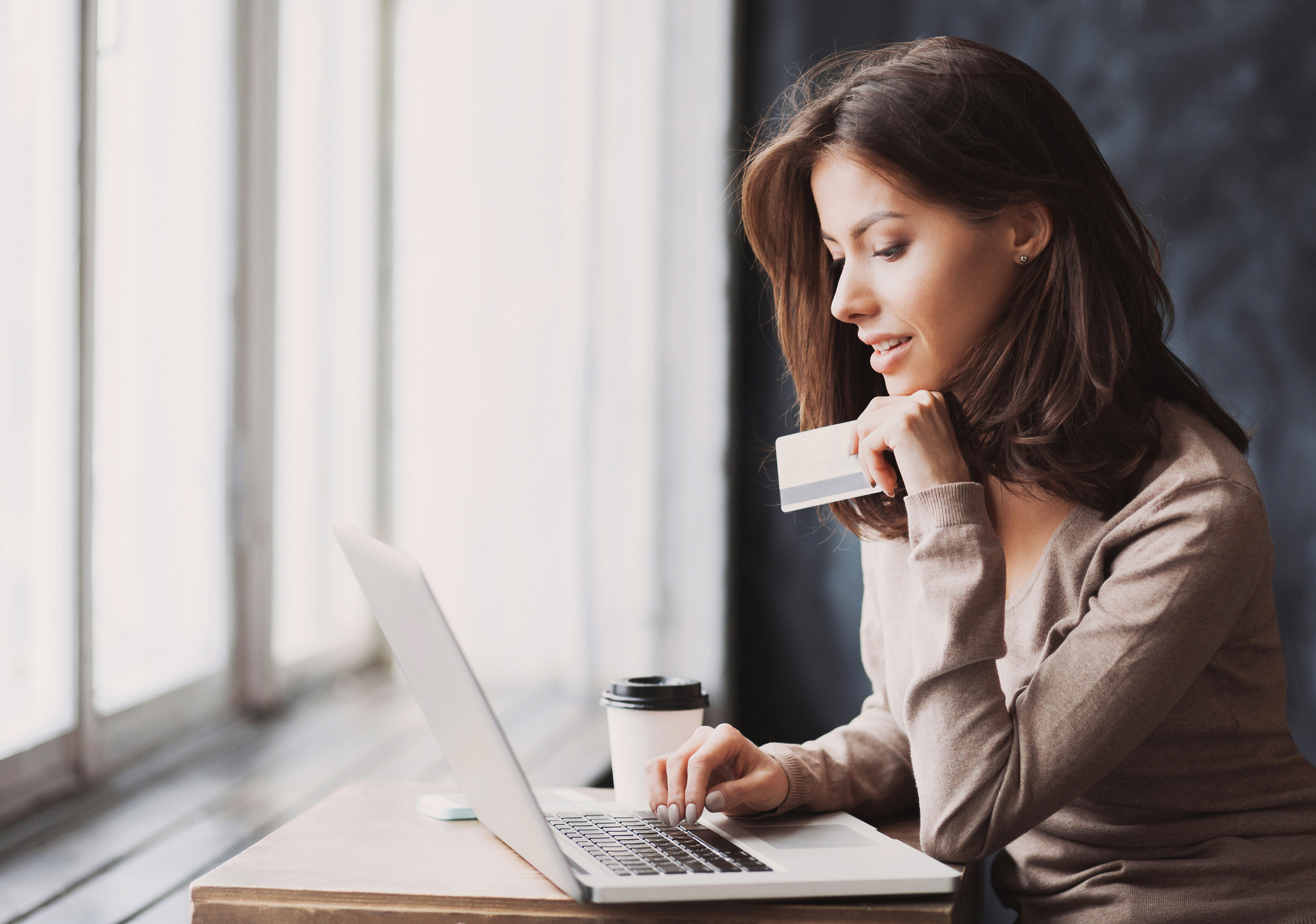 A woman using a laptop and holding a credit card.