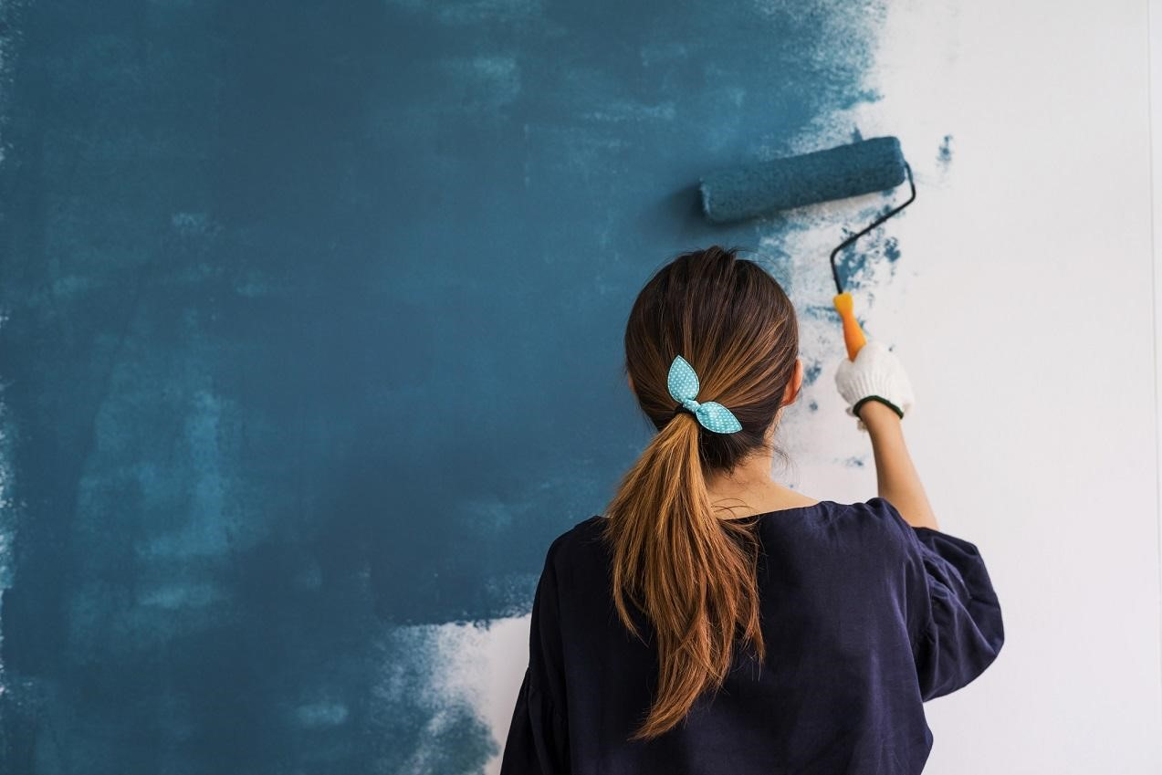 Woman painting home blue with a roller.