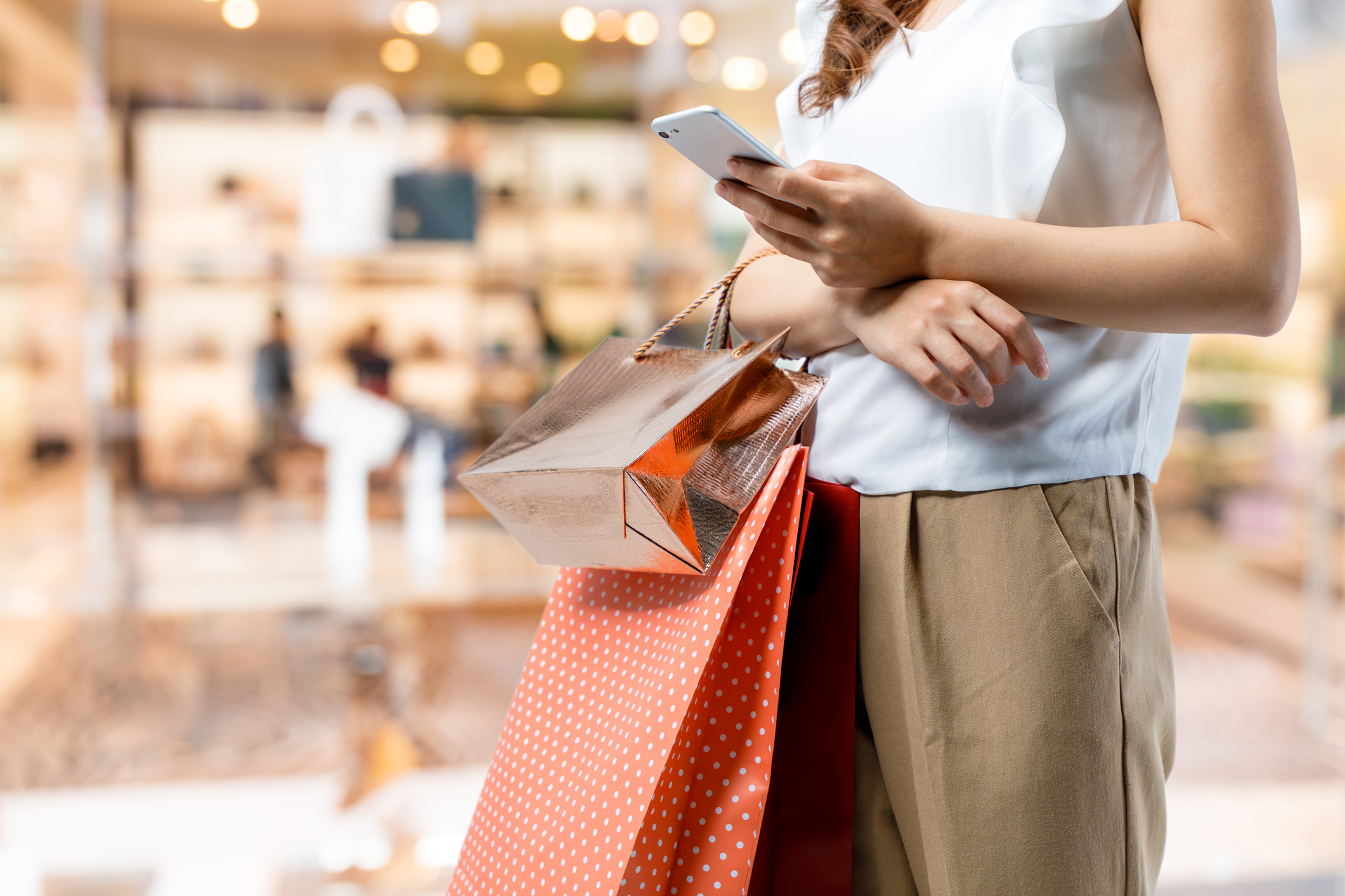 A woman holding shopping bags and looking at her phone.