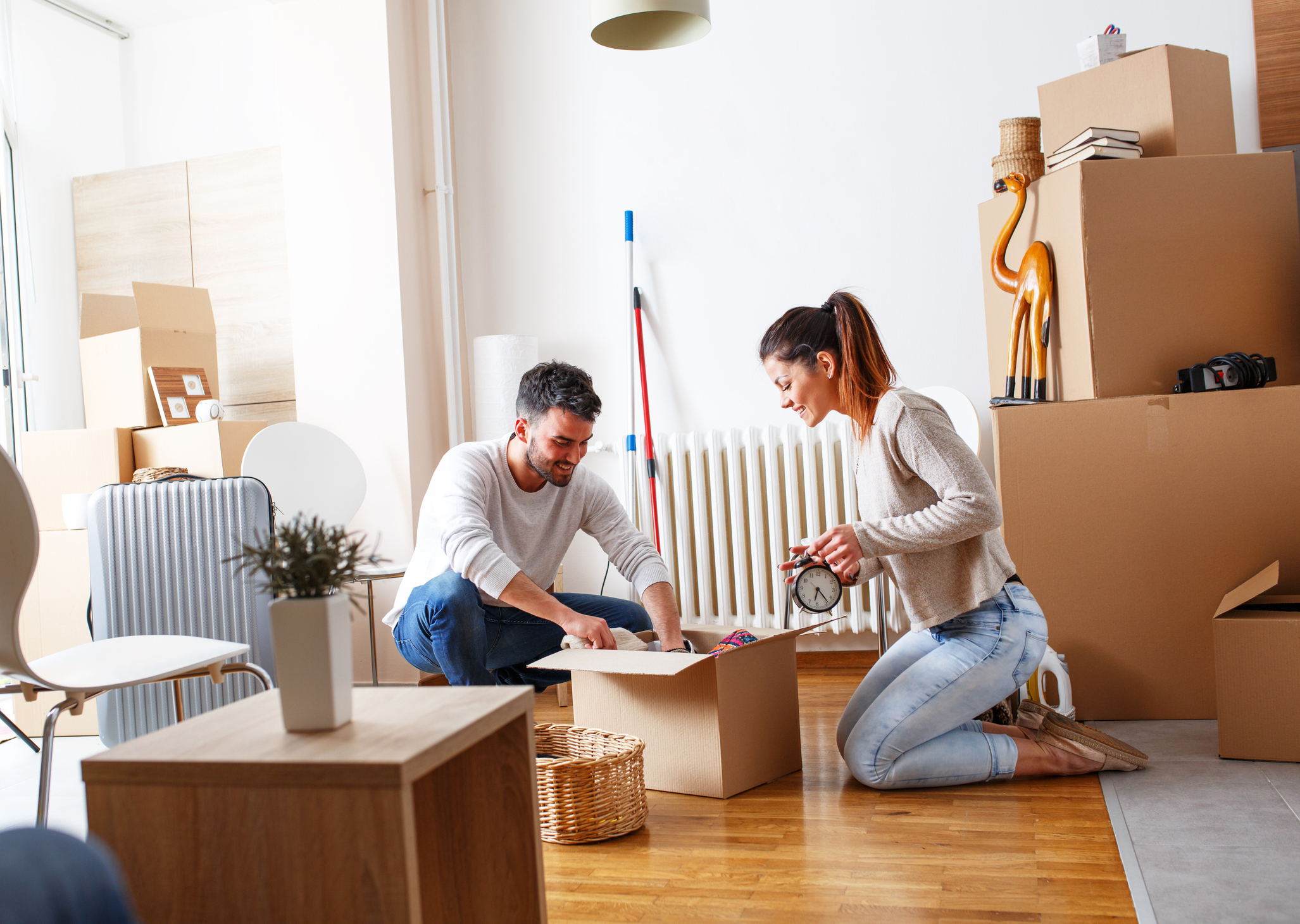 A young couple packing moving boxes in an apartment.