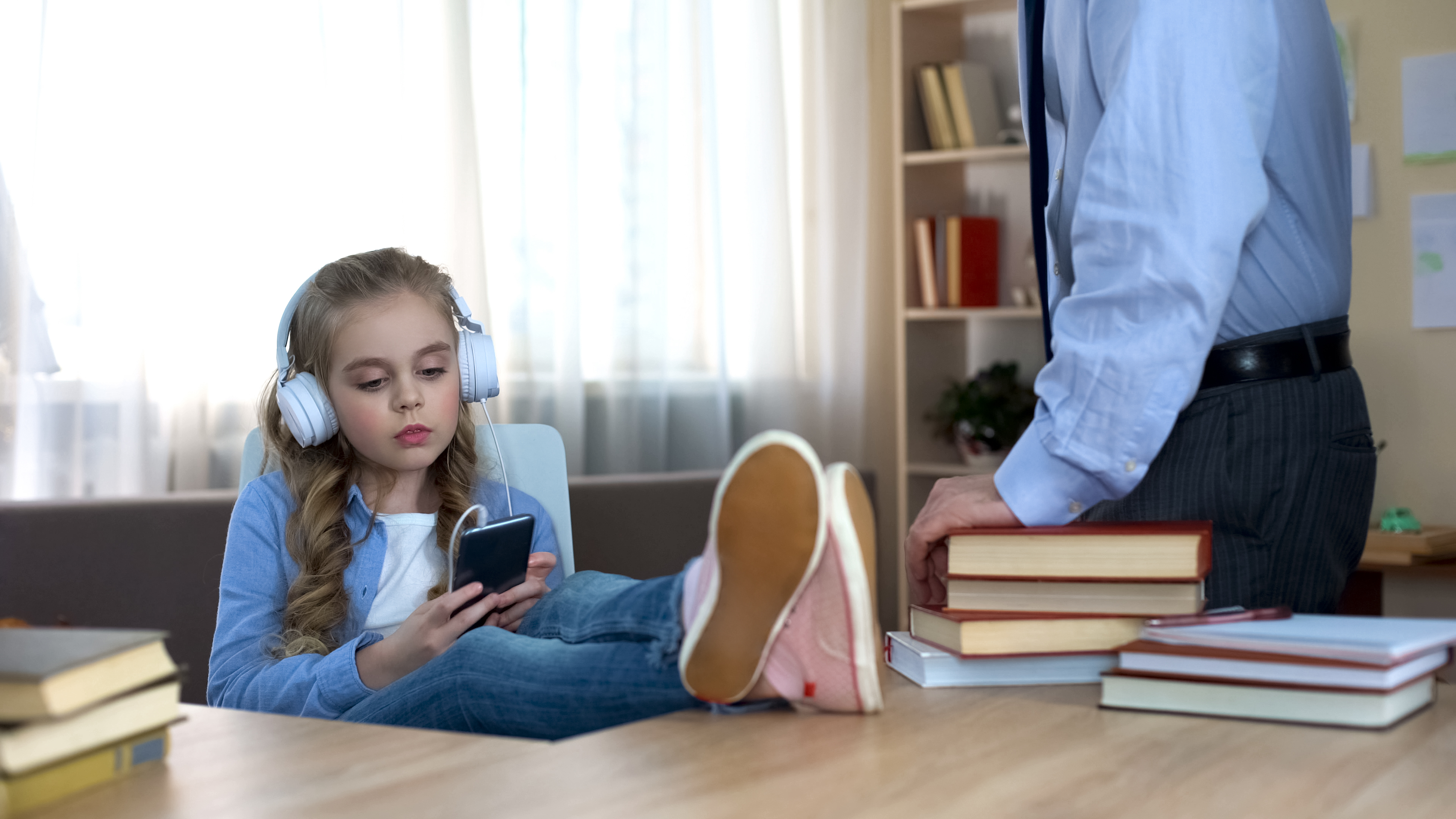 A young girl wearing headphones while ignoring her dad.