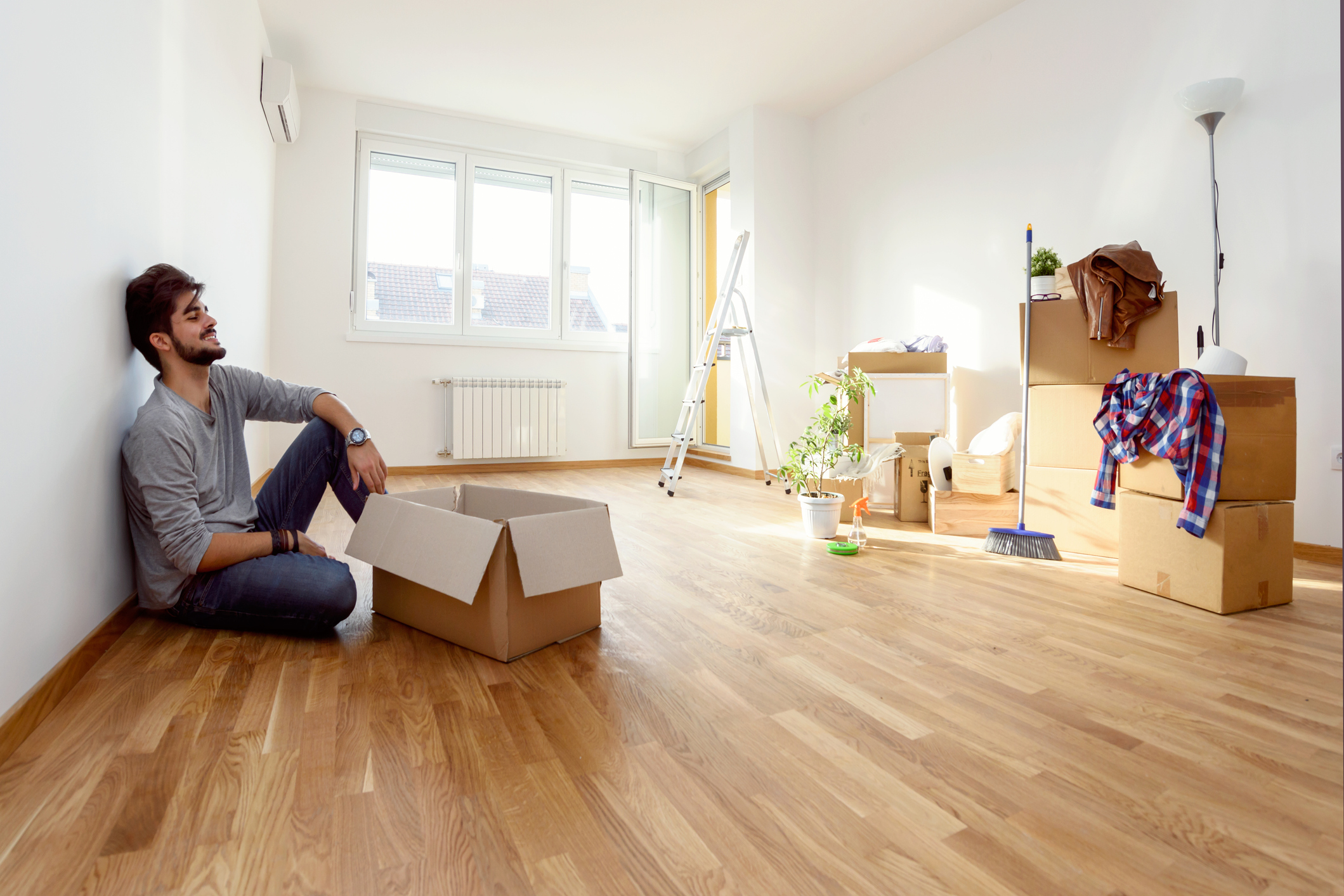 A young man in his new apartment filled with moving boxes.