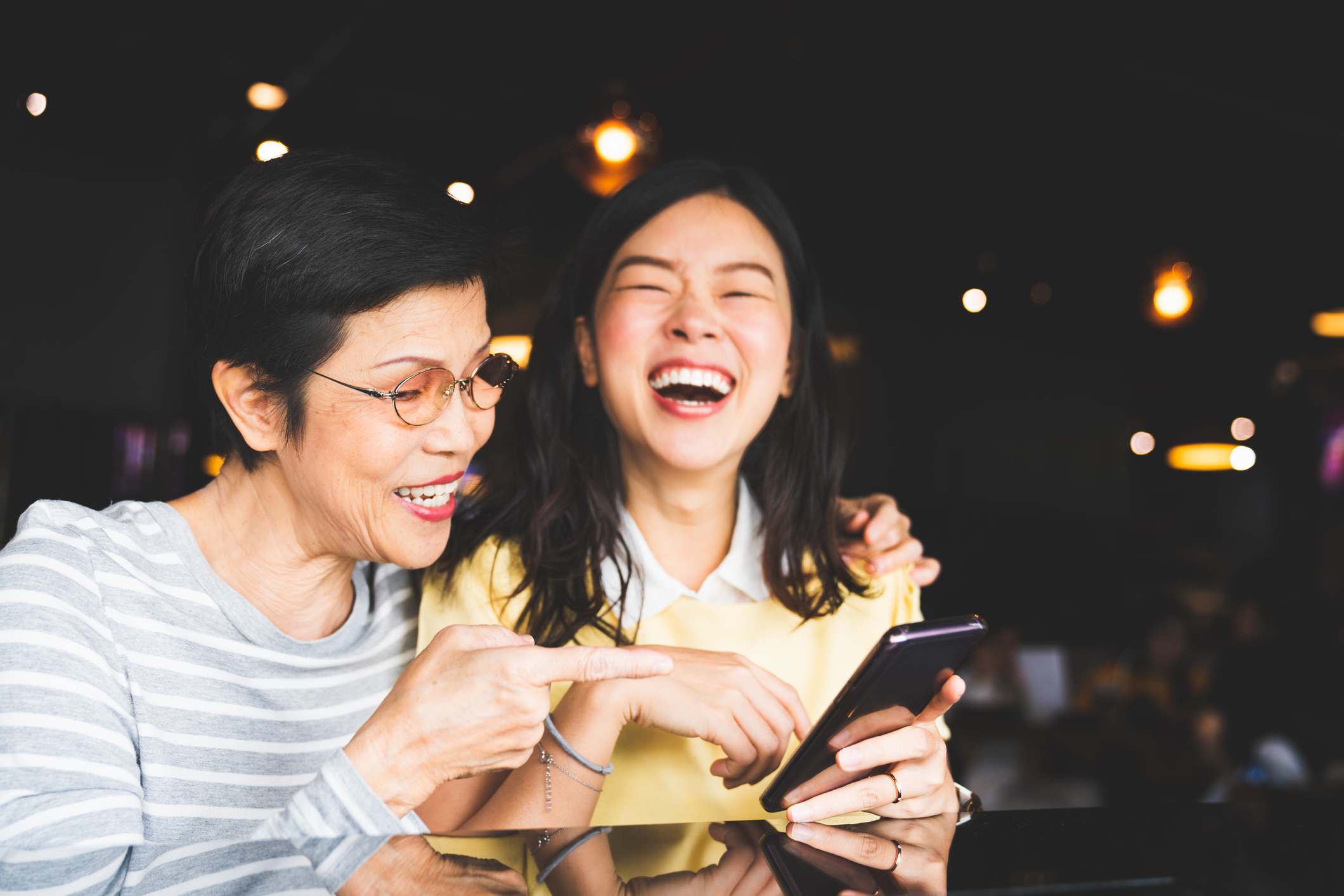 A young woman and her mother looking at a phone and laughing.