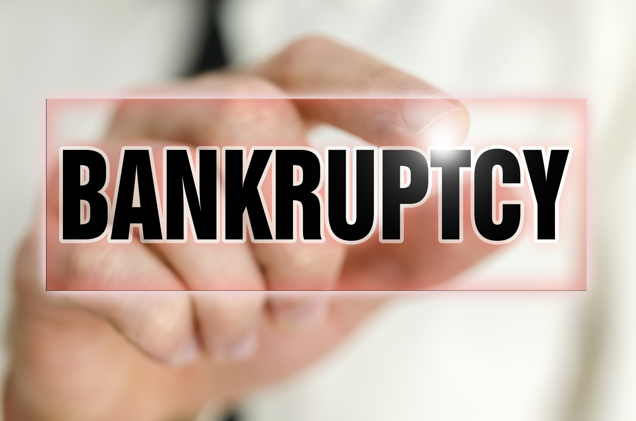 Man using finger to tap the word bankruptcy on a screen