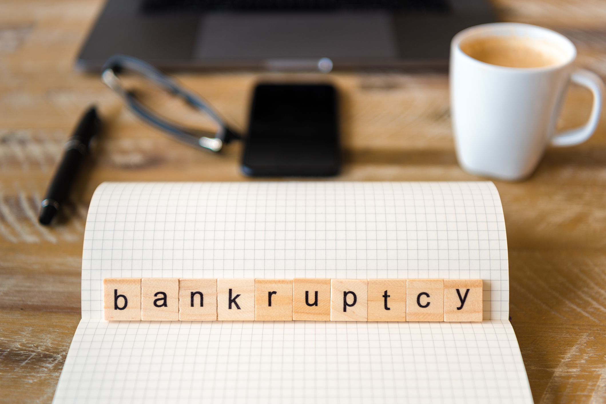 The word bankruptcy spelled out in tiles on a pad of paper
