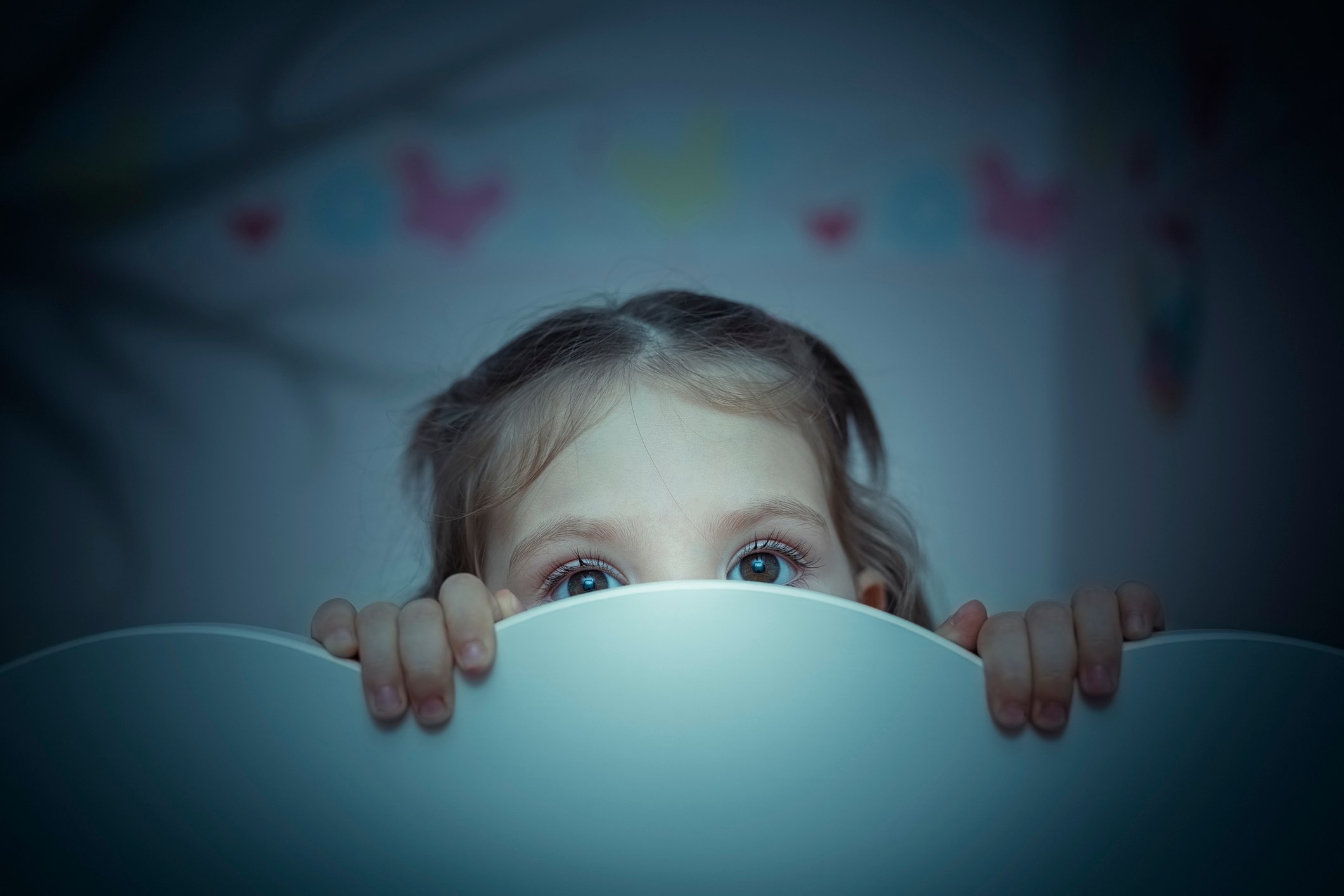 Small child peering out from behind headboard.