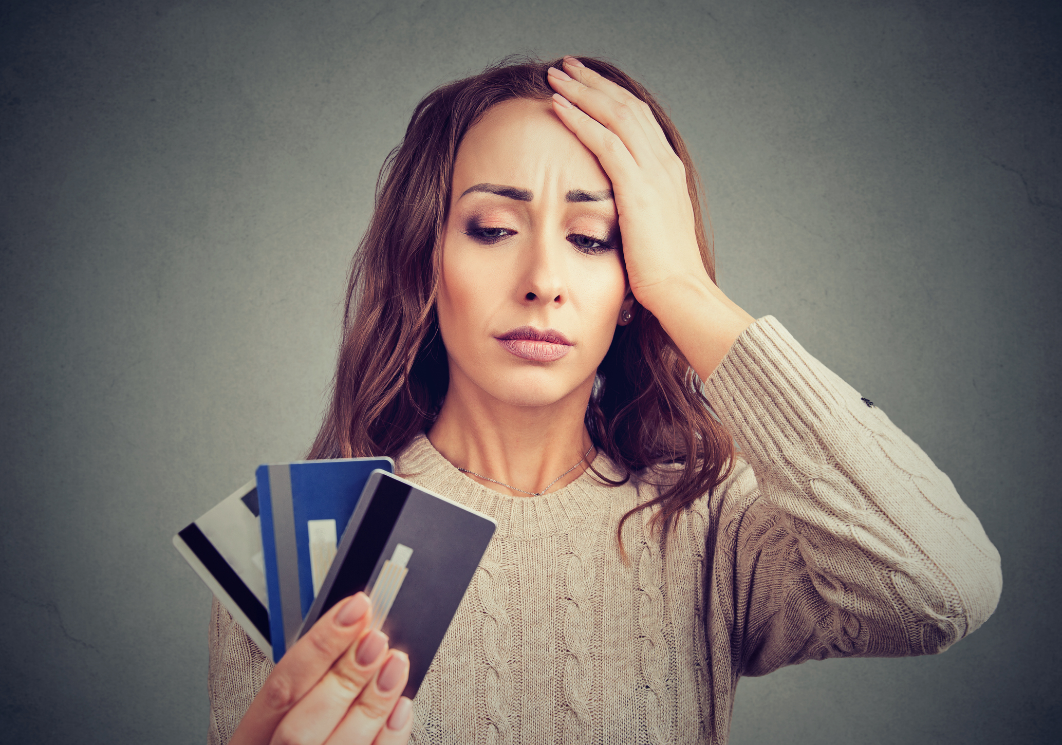Woman holding three credit cards and holding her head in dismay.