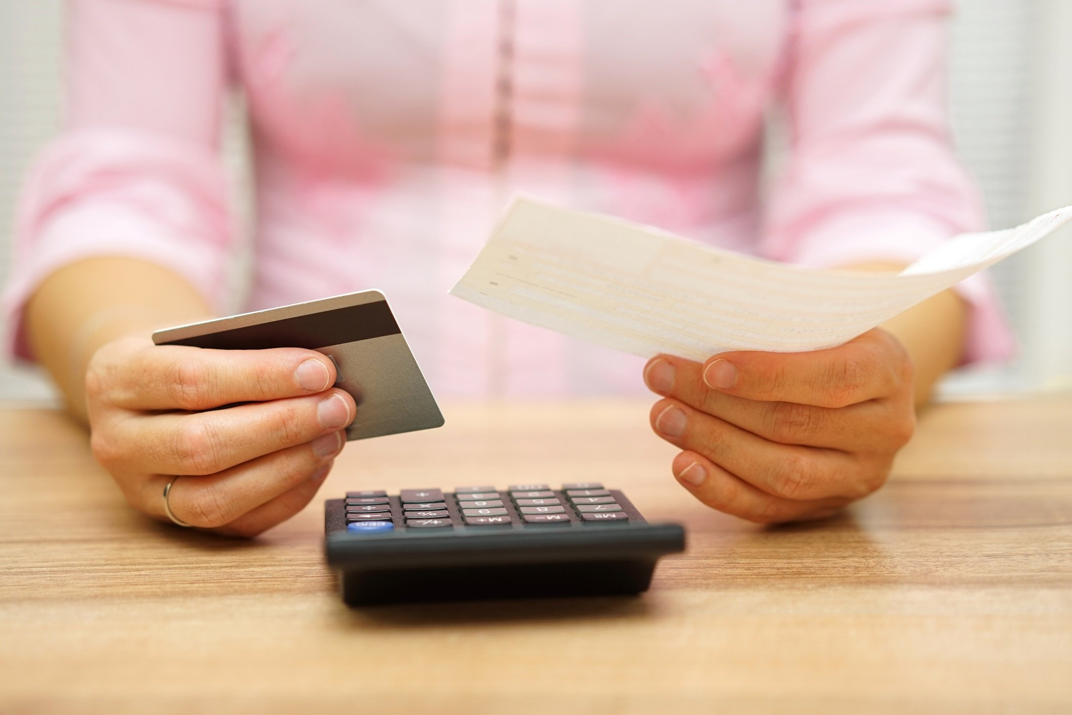 woman holding credit card and piece of paper looking at calculator