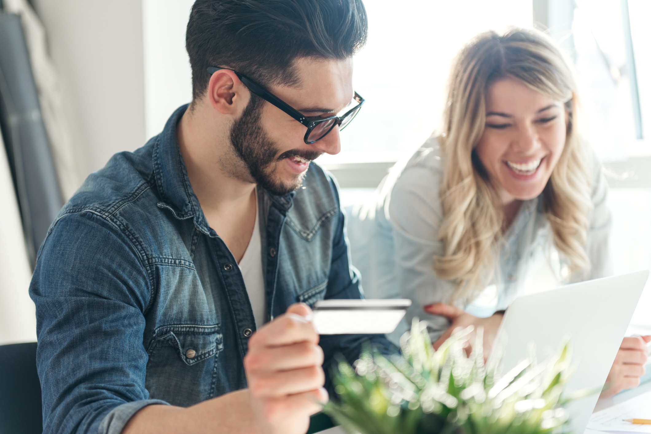 Young couple smiles while holding a credit card and looking at laptop screen.