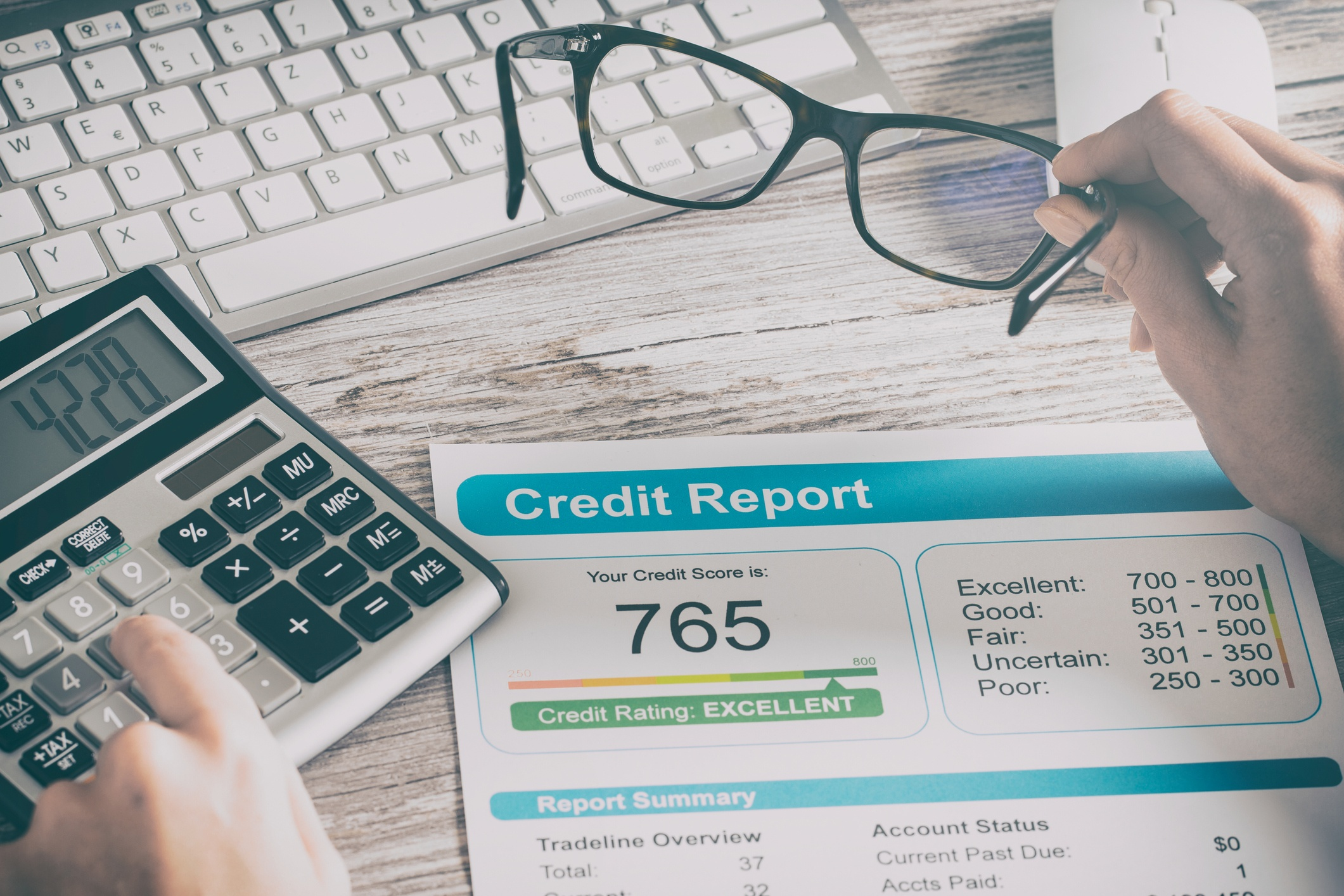 Credit report that reads 765 on a desk where someone is typing on a calculator and their holding glasses