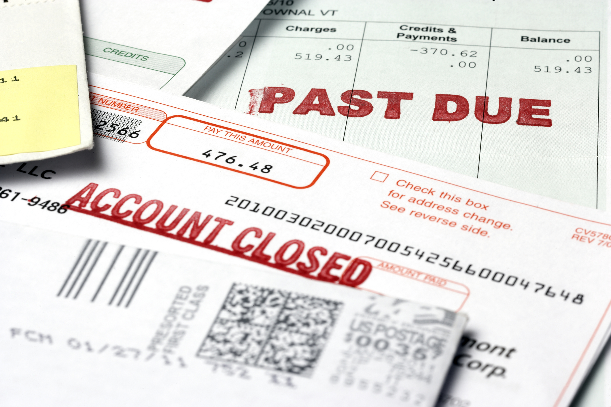 "Financial paperwork including a bill labeled ""Past Due"" and another labeled ""Account Closed"""