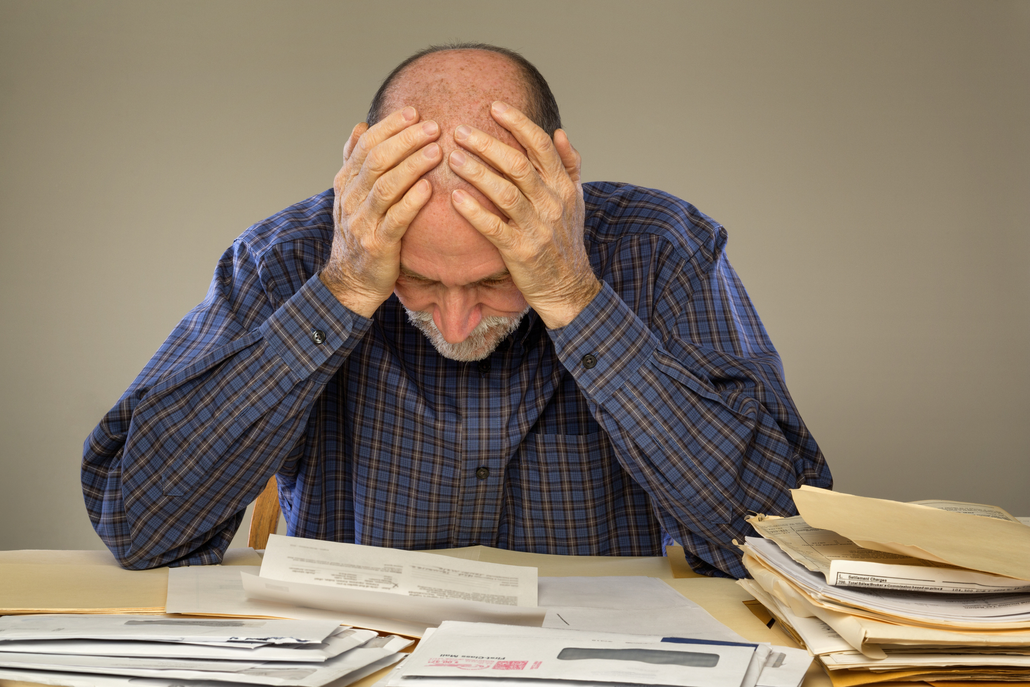 Frustrated man looking at bills on a desk.