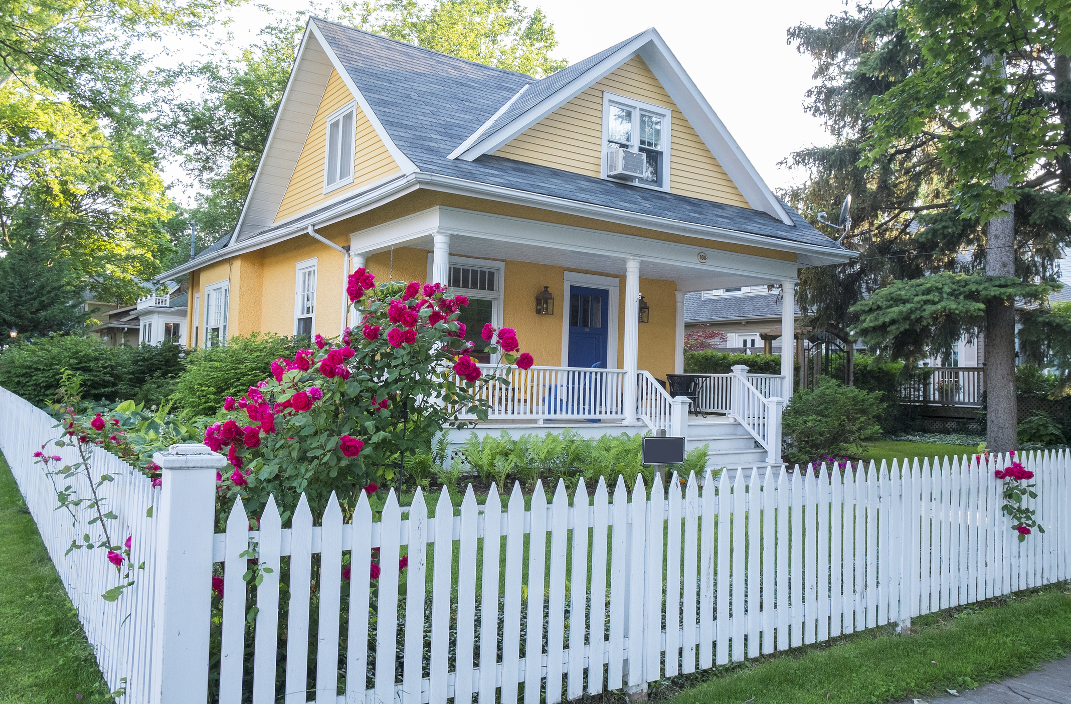 A yellow house with a white picket fence.