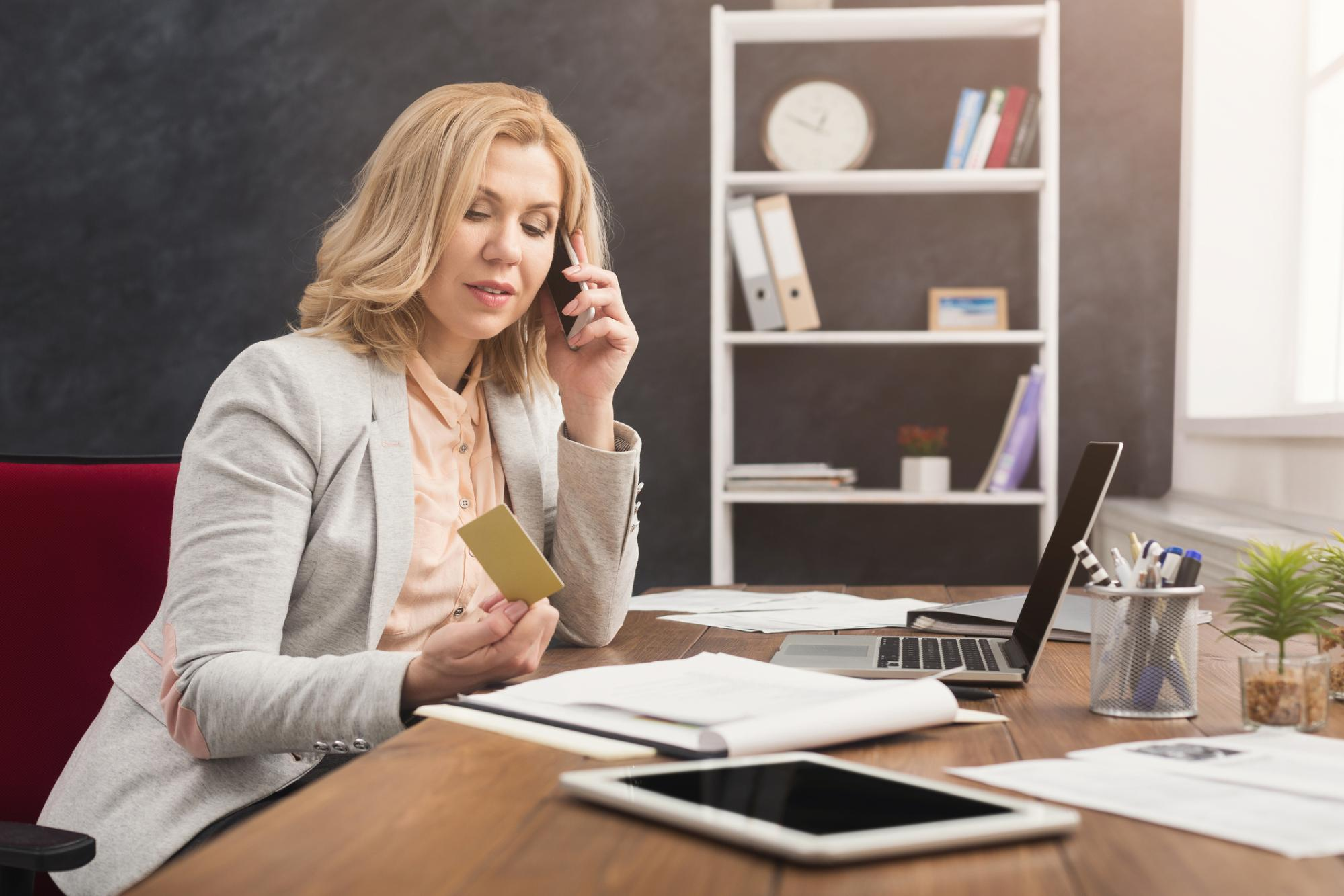 woman on the phone looking at credit card