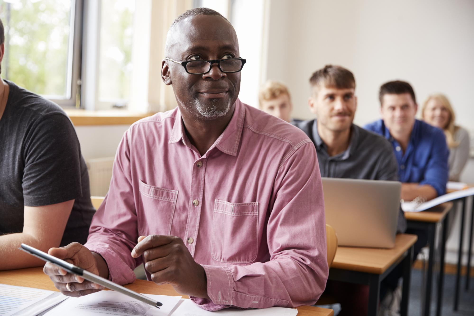 middle-aged man sitting in class room among youthful students
