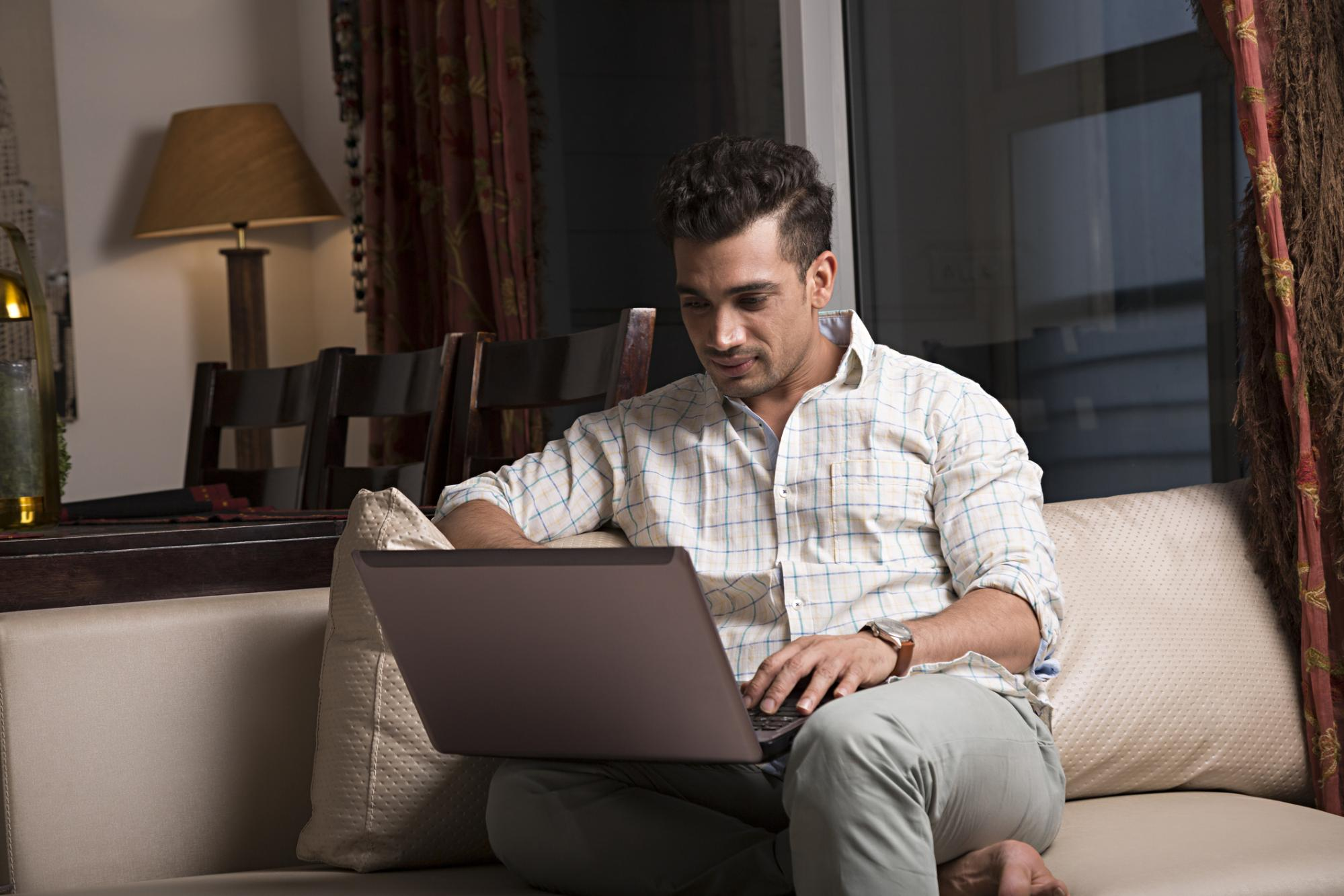 millennial looking at computer on couch