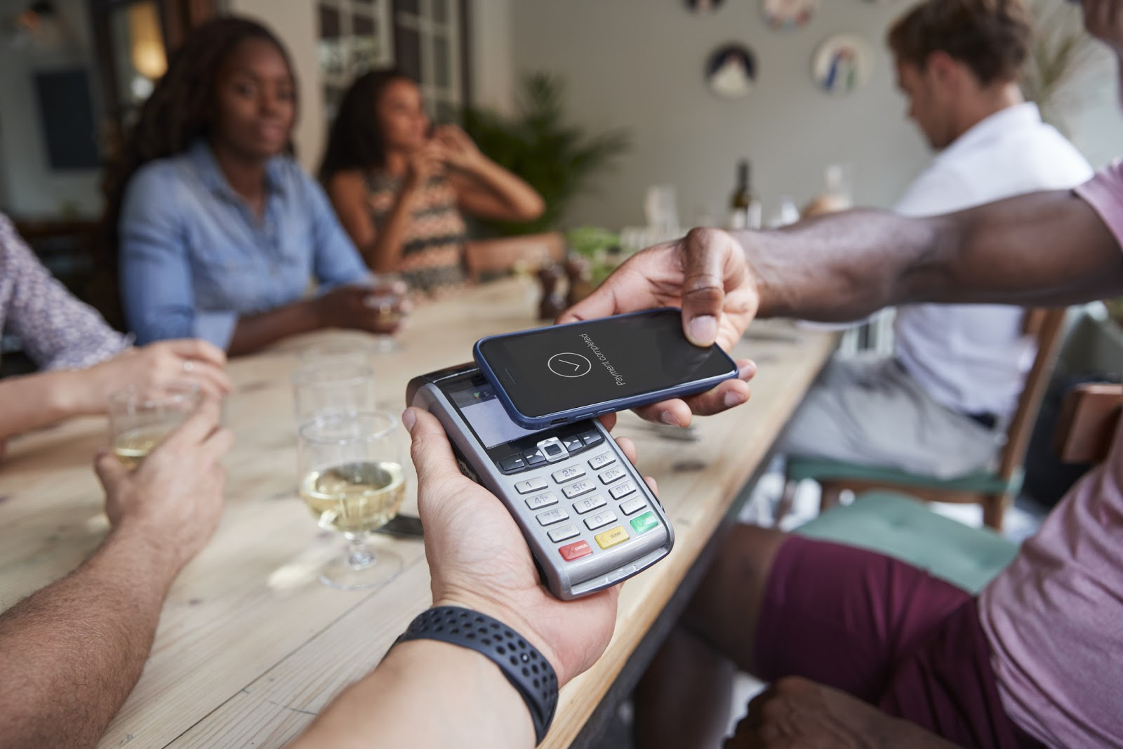 family at restaurant paying with mobile payment app on phone