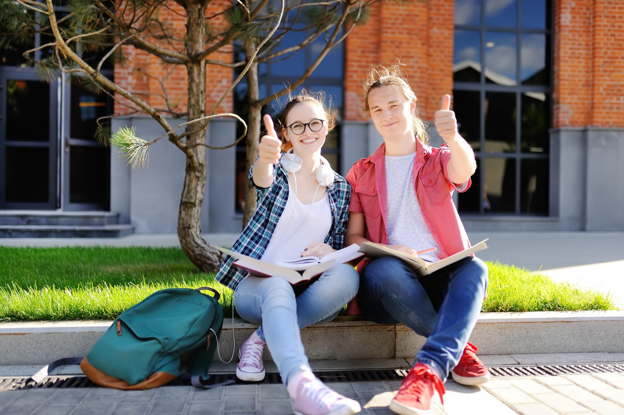 male and female student smiling and giving a thumbs up