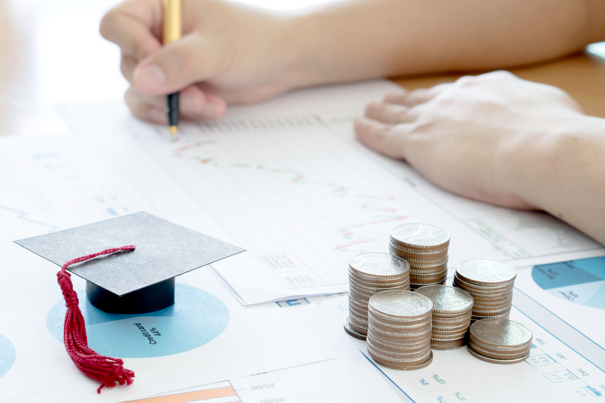 person writing on a piece of paper with a small graduation cap and stacks of coins in the foreground