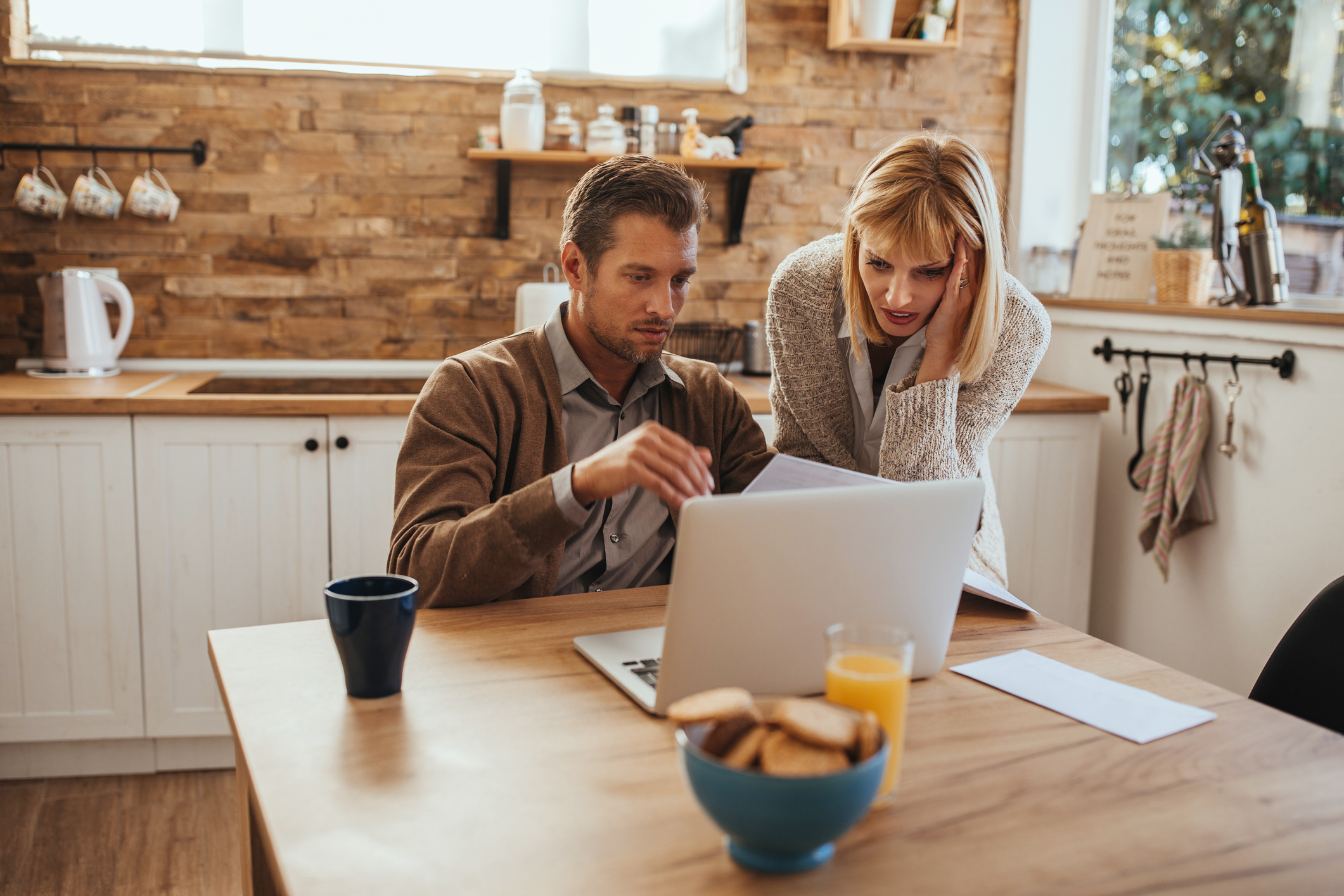 Man and woman worriedly looking at laptop