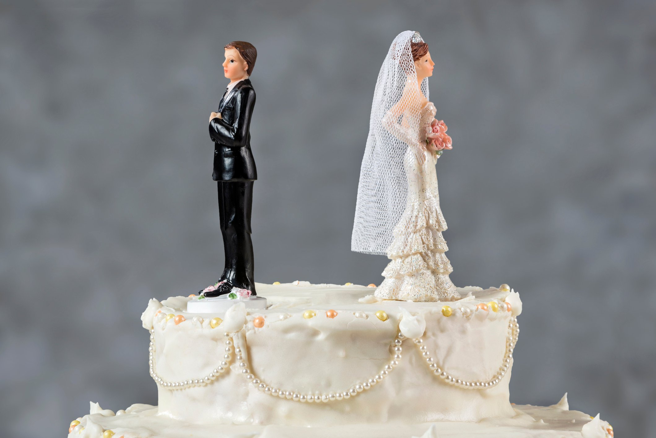 Wedding cake with angry married spouse figures on top of it.