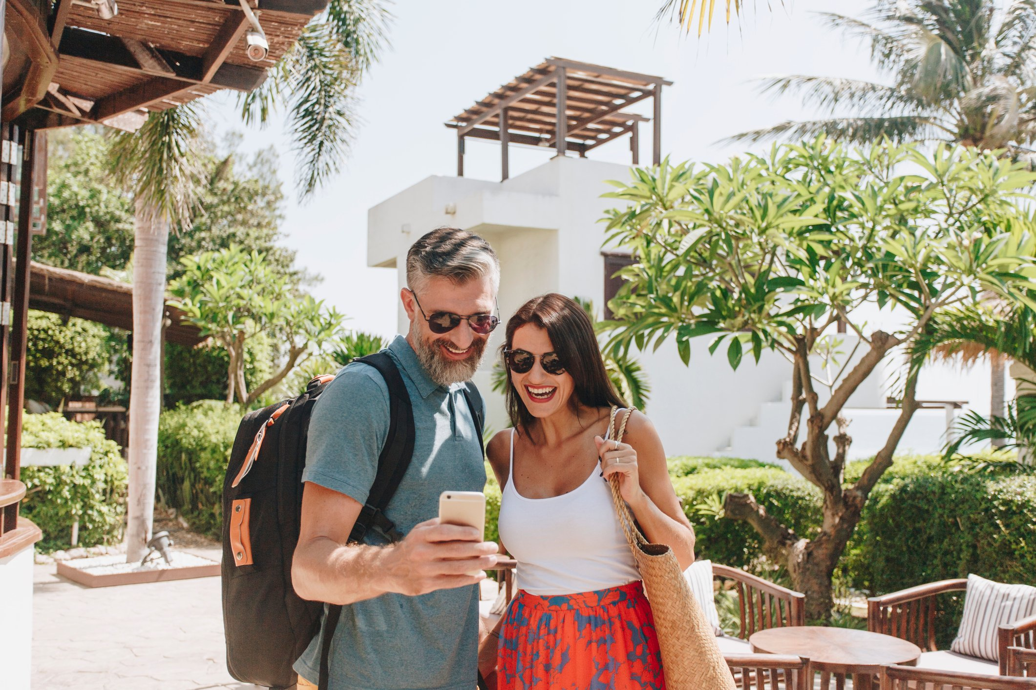 mature man and woman taking a selfie in front of a hotel and palm trees
