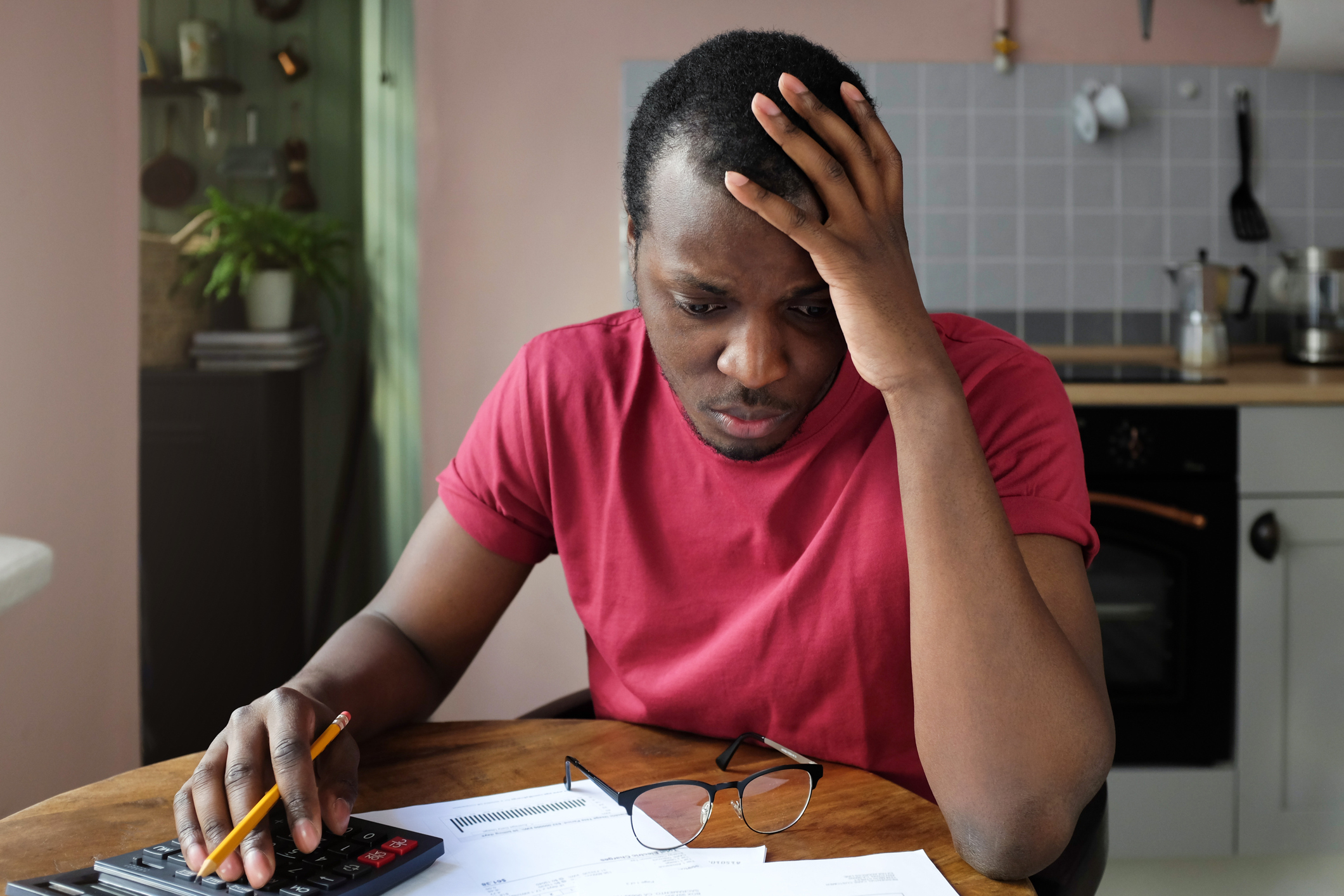 Man sitting at table, holding head while looking at documents and typing on calculator