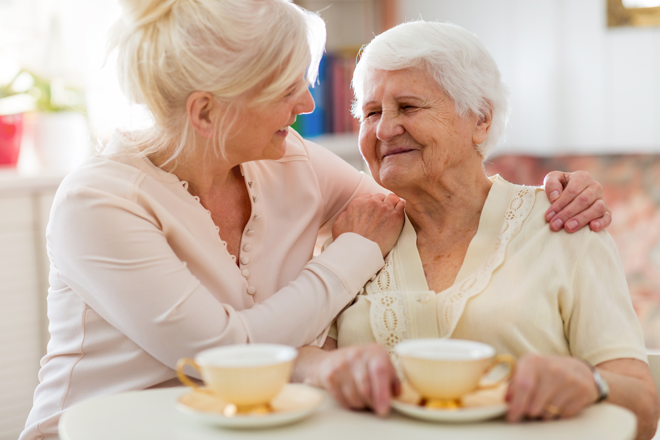 middle-aged woman holding her elderly mother and smiling while sitting at a kitchen table