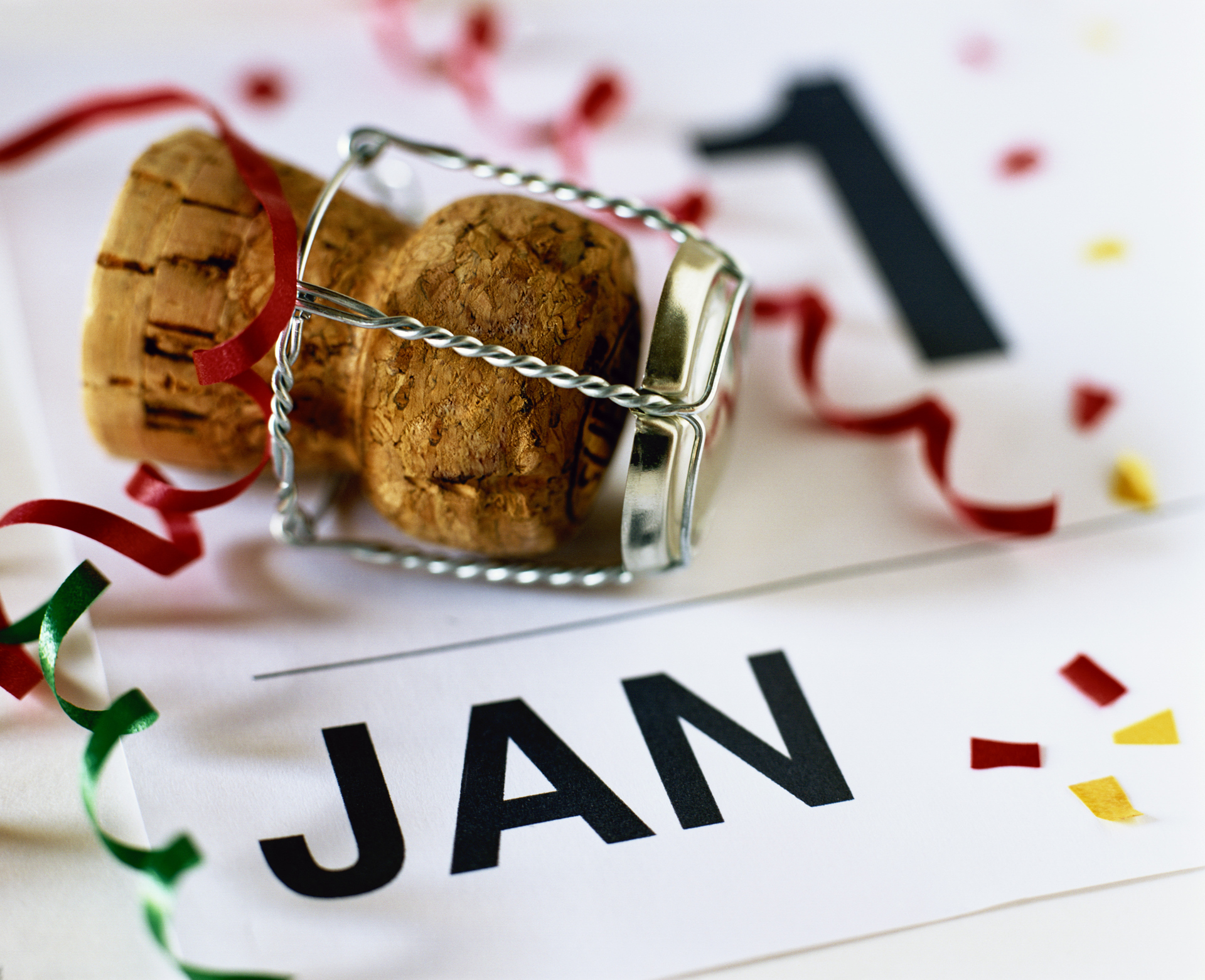 Calendar labeled January 1 with champagne cork and confetti on it.