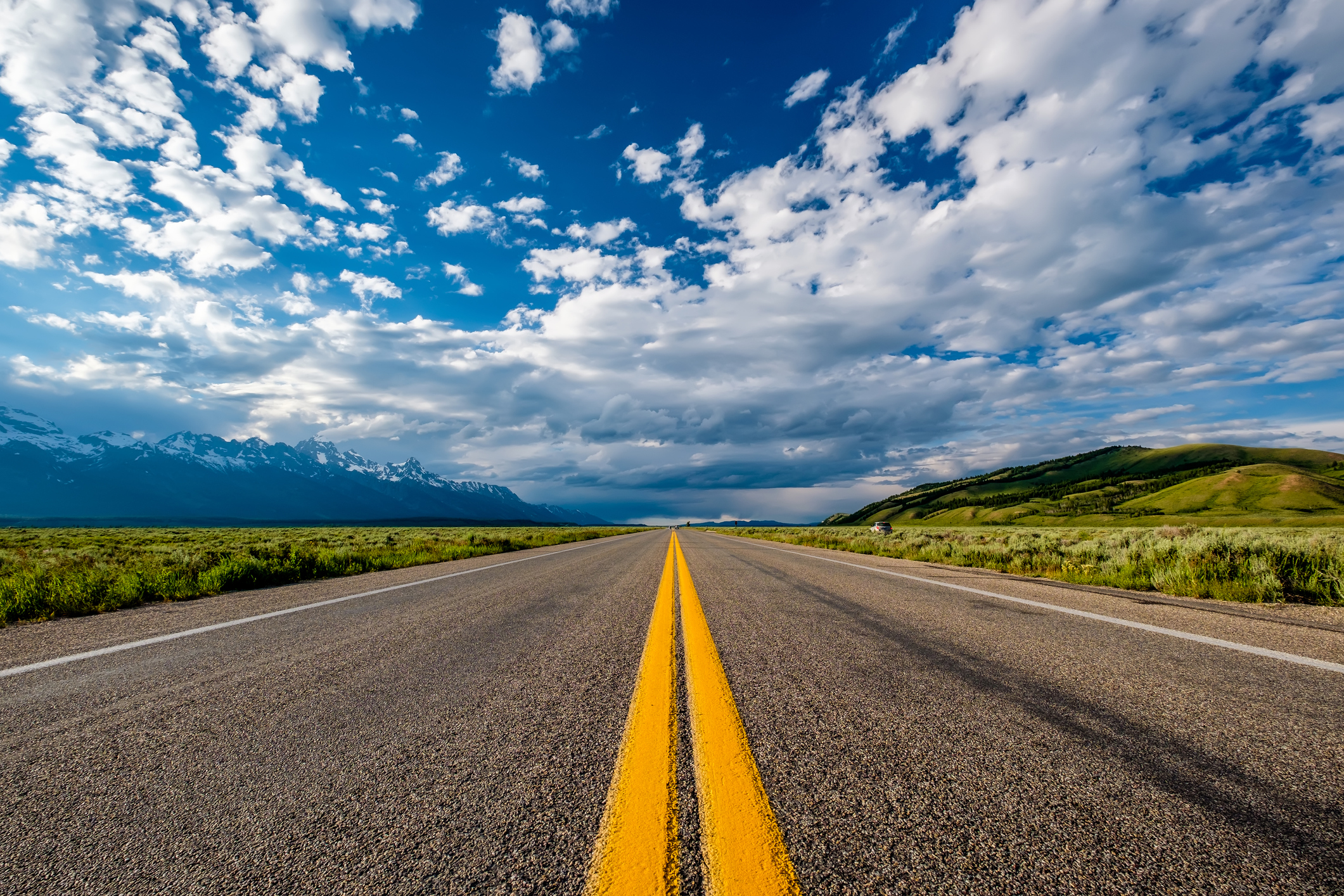 Open road with double yellow lines and blue sky.