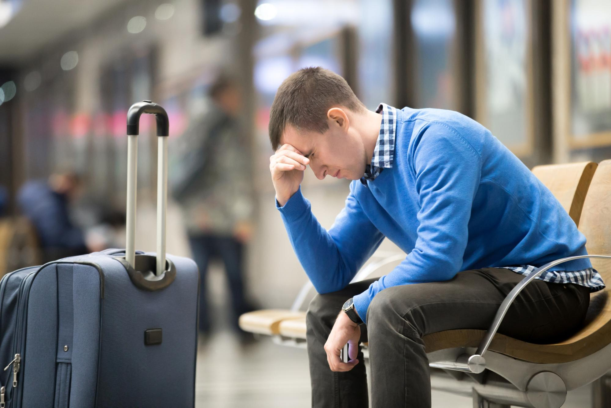 pained young man beside suitcase in airport