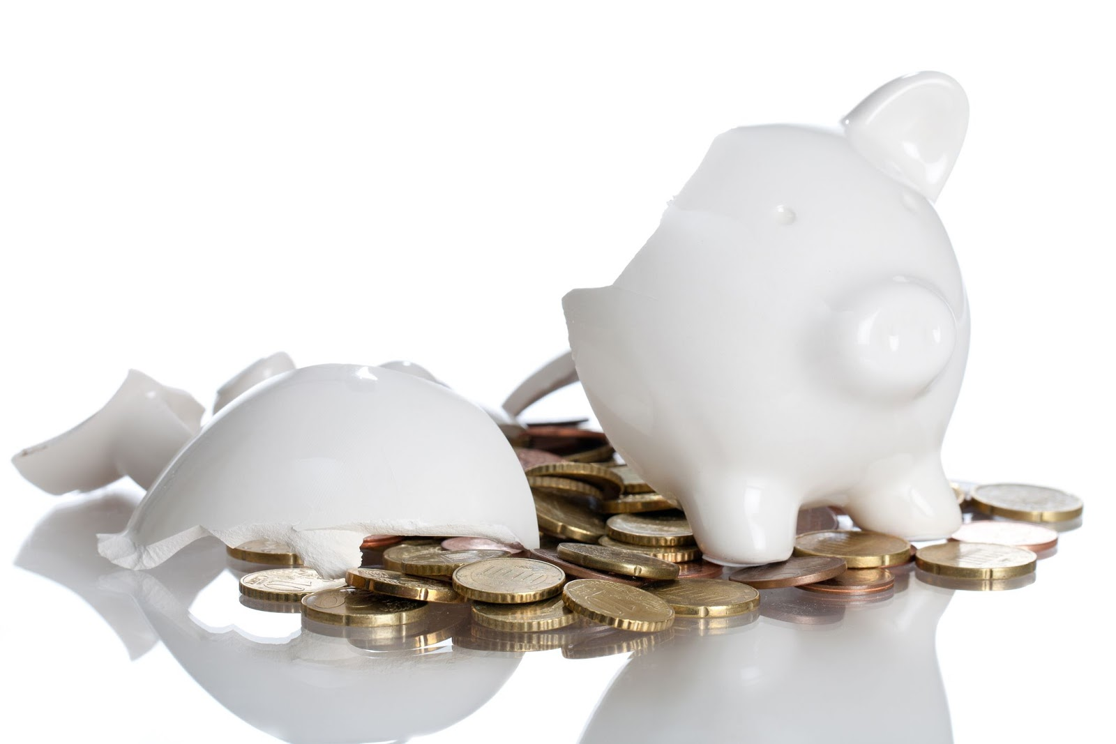 A white piggy bank broken with coins spilling out.