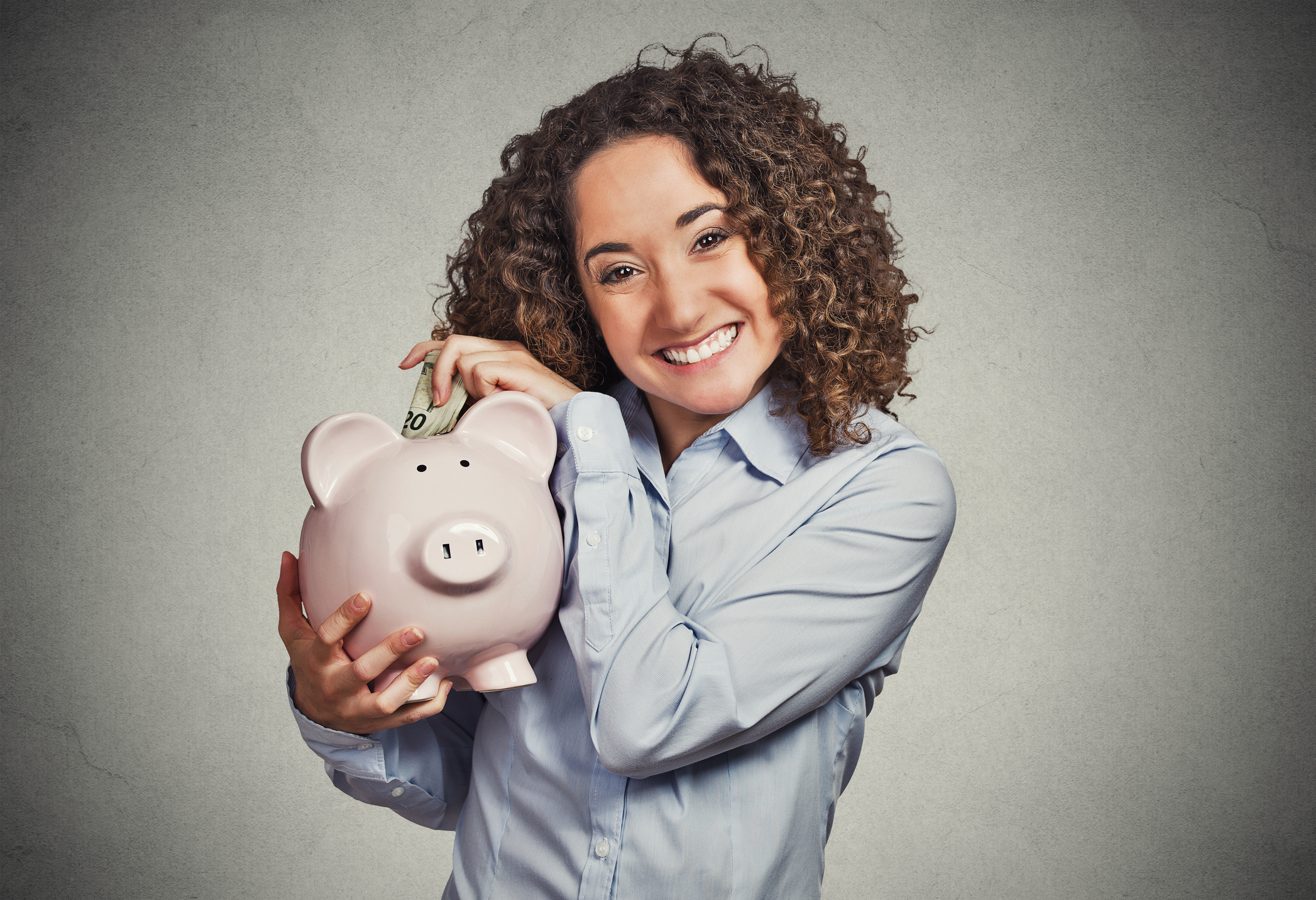A smiling woman putting money into a piggy bank.