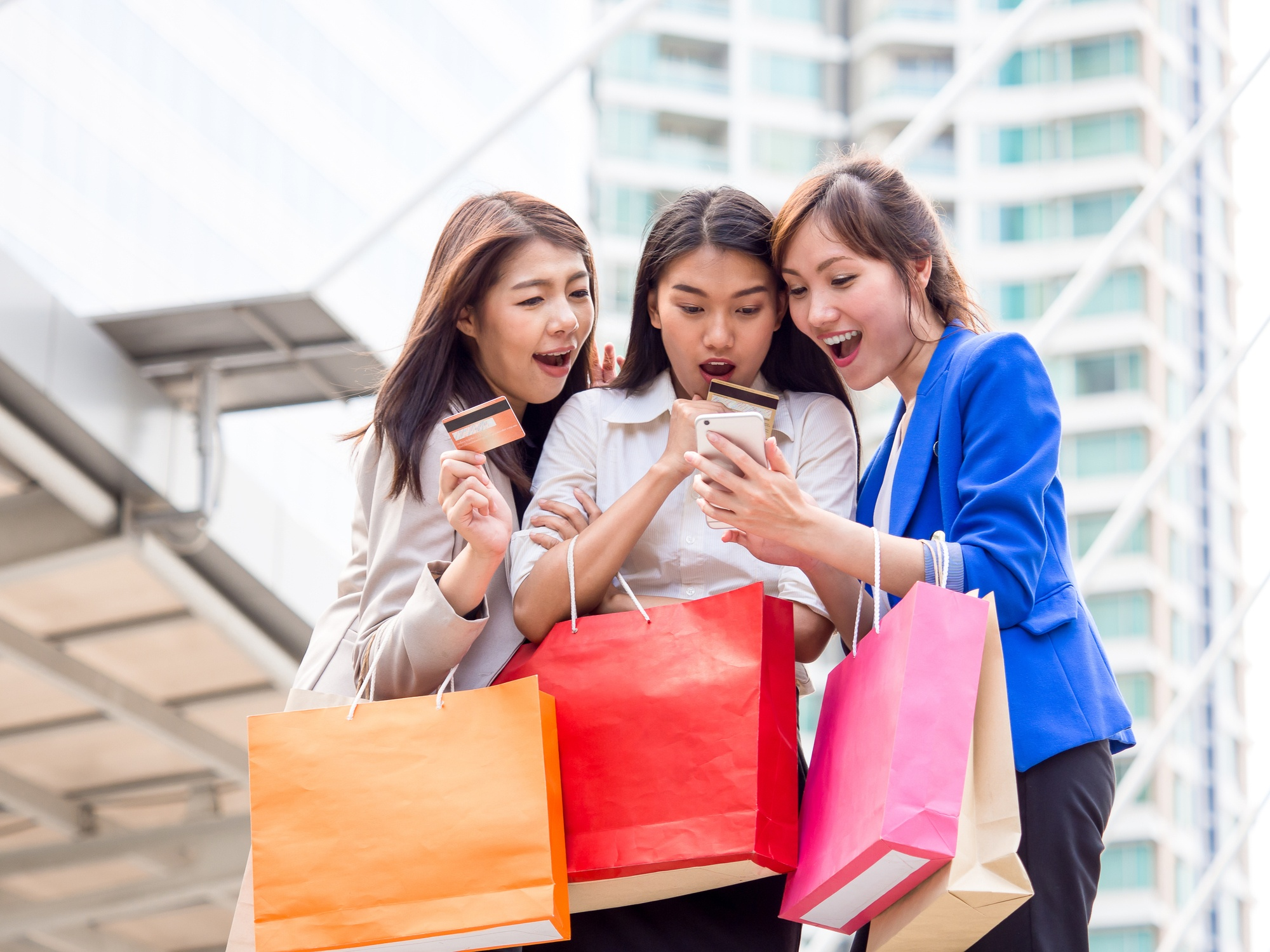 three girls with shopping bags and credit cards looking at phone