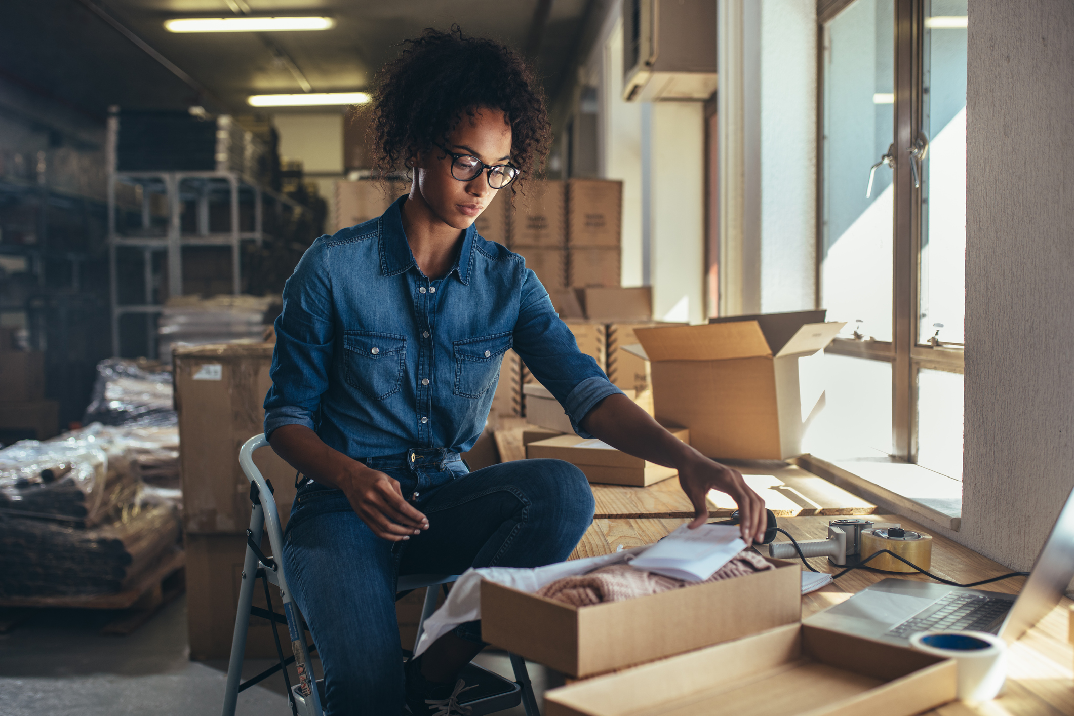 woman packing box at small business