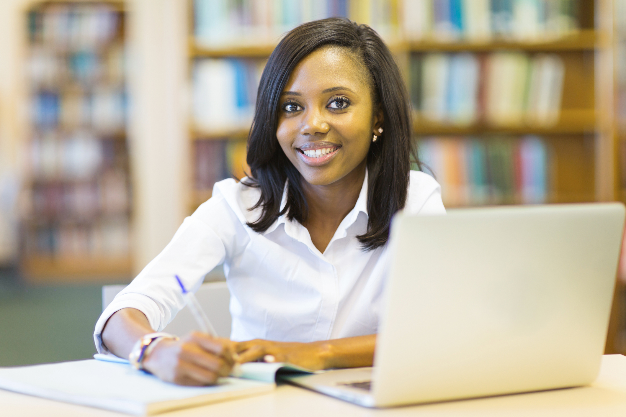 Smiling young woman in library at laptop writing in a notebook