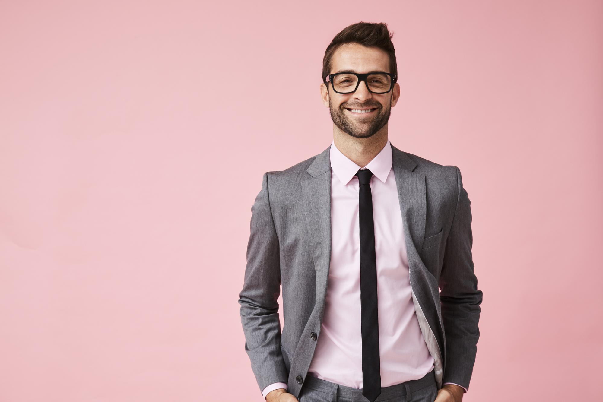 smiling young man in suit and glasses