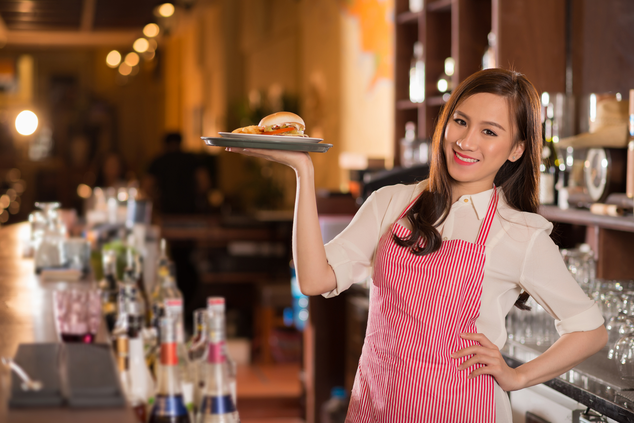 Waitress in red apron holding food