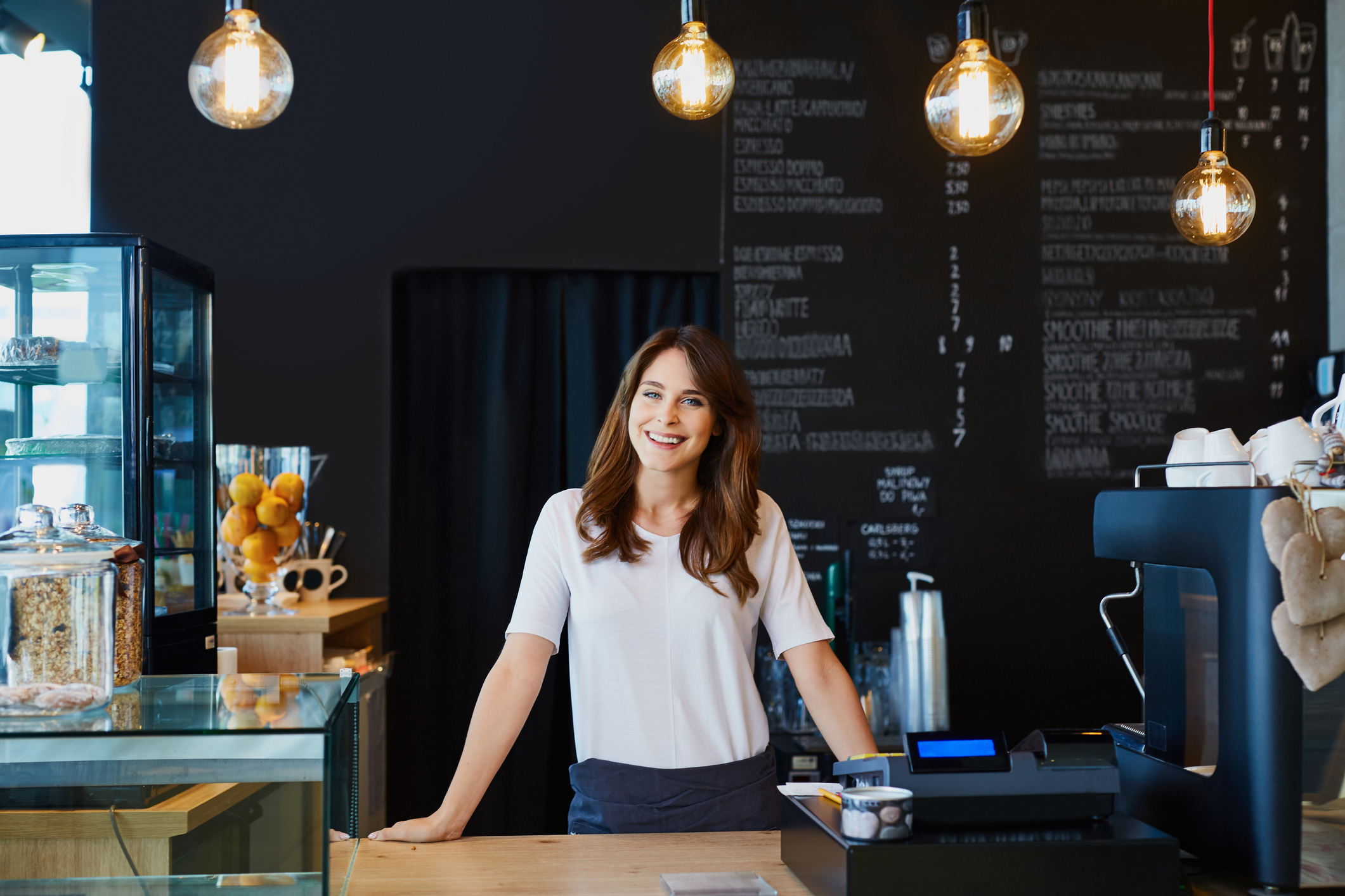 smiling young woman standing behind the counter in a cafe