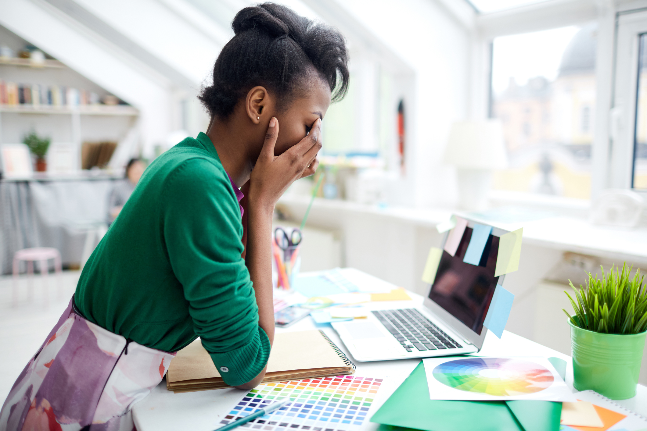 Stressed young woman sitting at a desk in front of laptop with her face in her hands