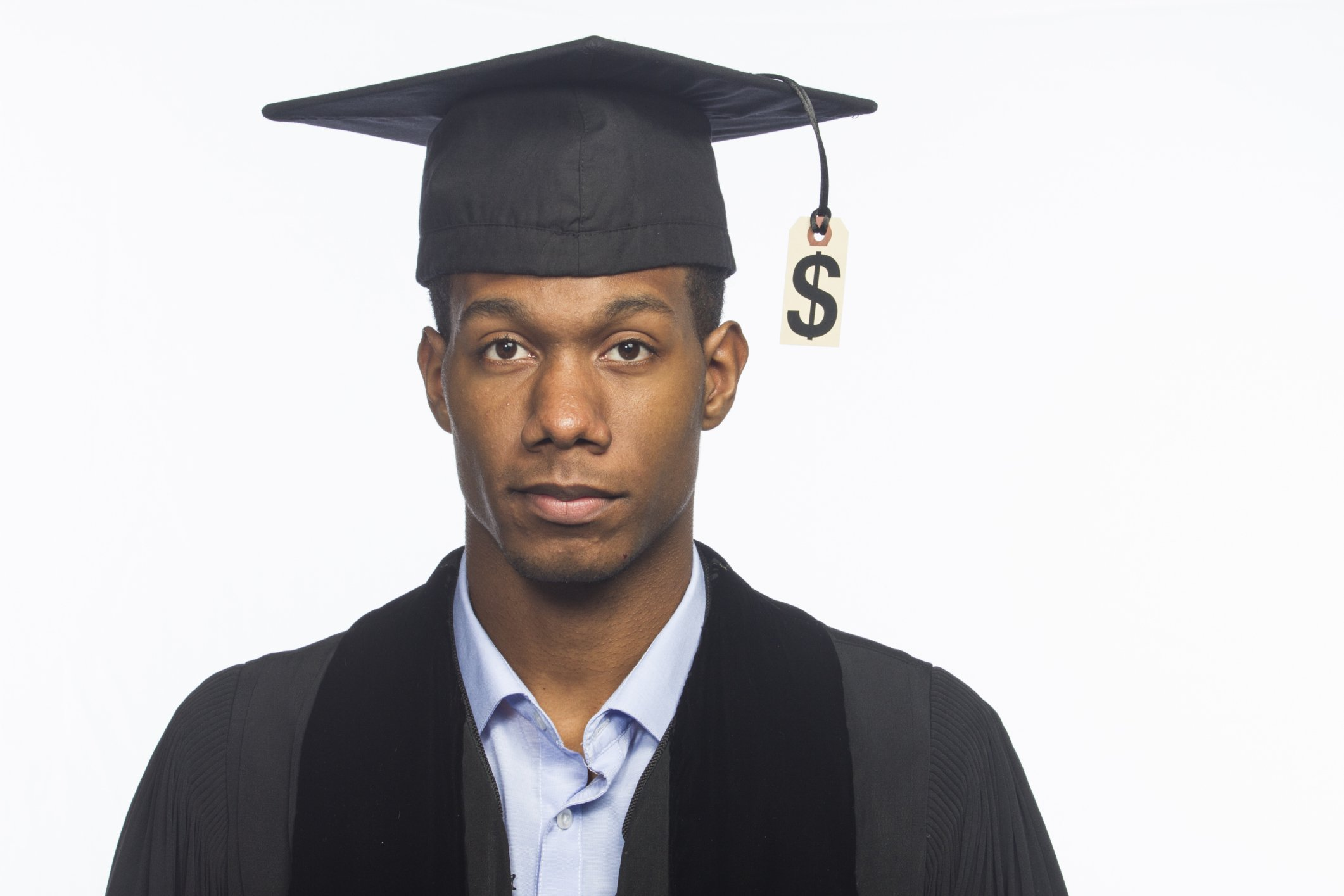 young college graduate wearing robe and mortarboard with price tag hanging from it