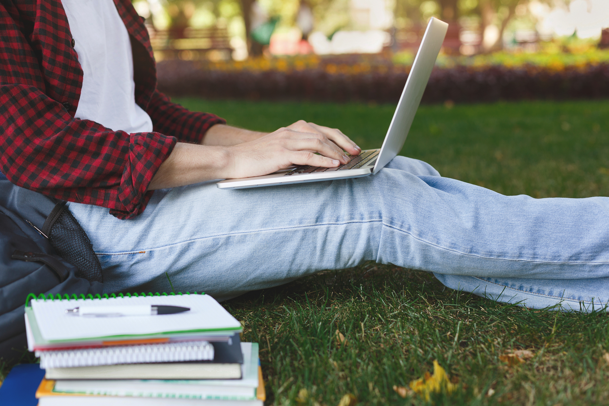 Man in jeans and open plaid shirt sitting on grass typing on laptop
