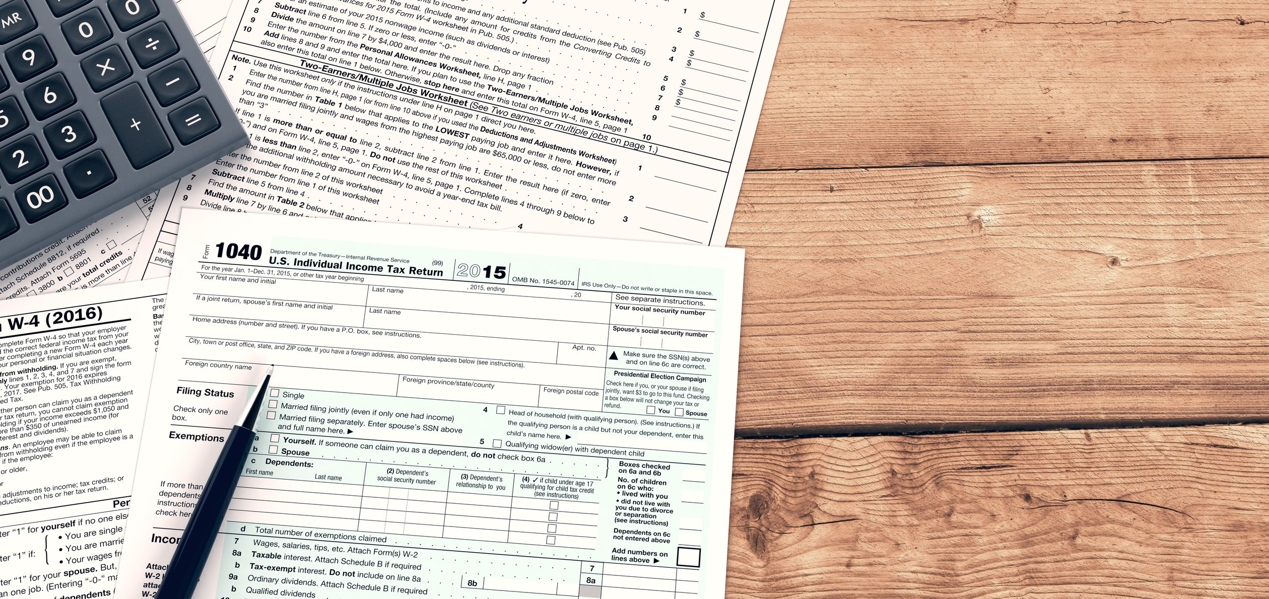 Tax forms with calculator and pen on wooden surface.