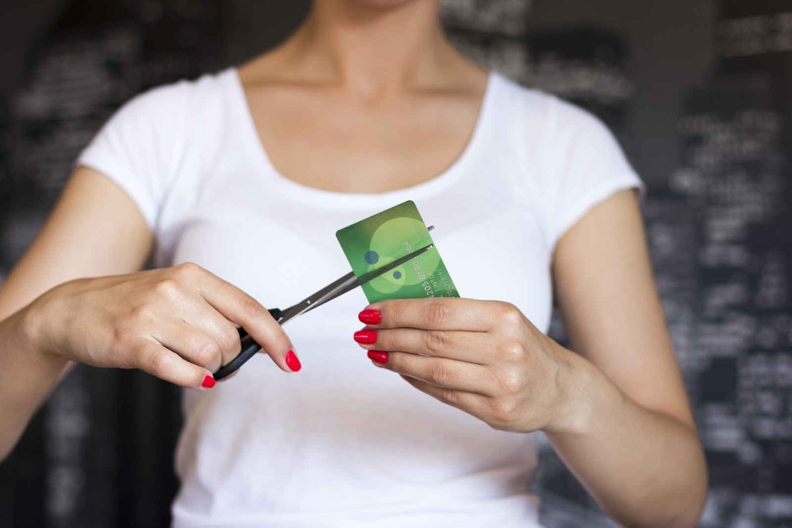 Woman cutting a credit card with scissors