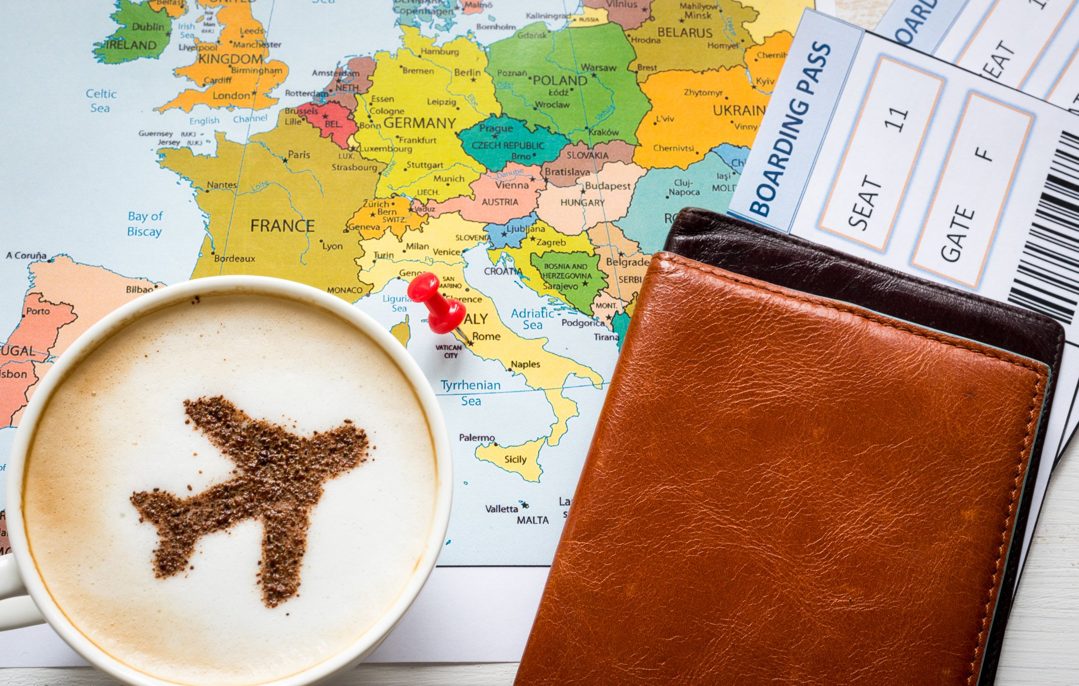 Cup of coffee with plane image in it sitting on top of map and next to a boarding pass.