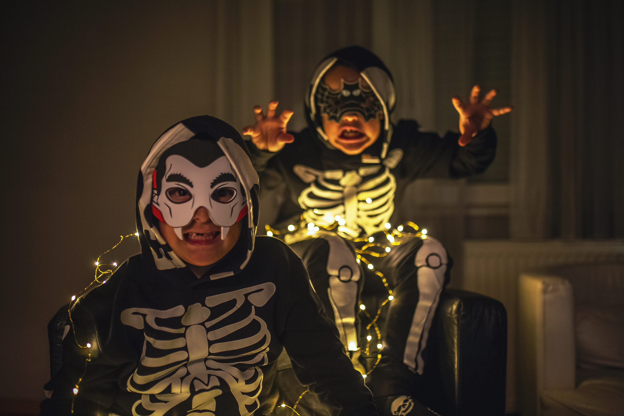 two young boys in Halloween costumes making scary faces.