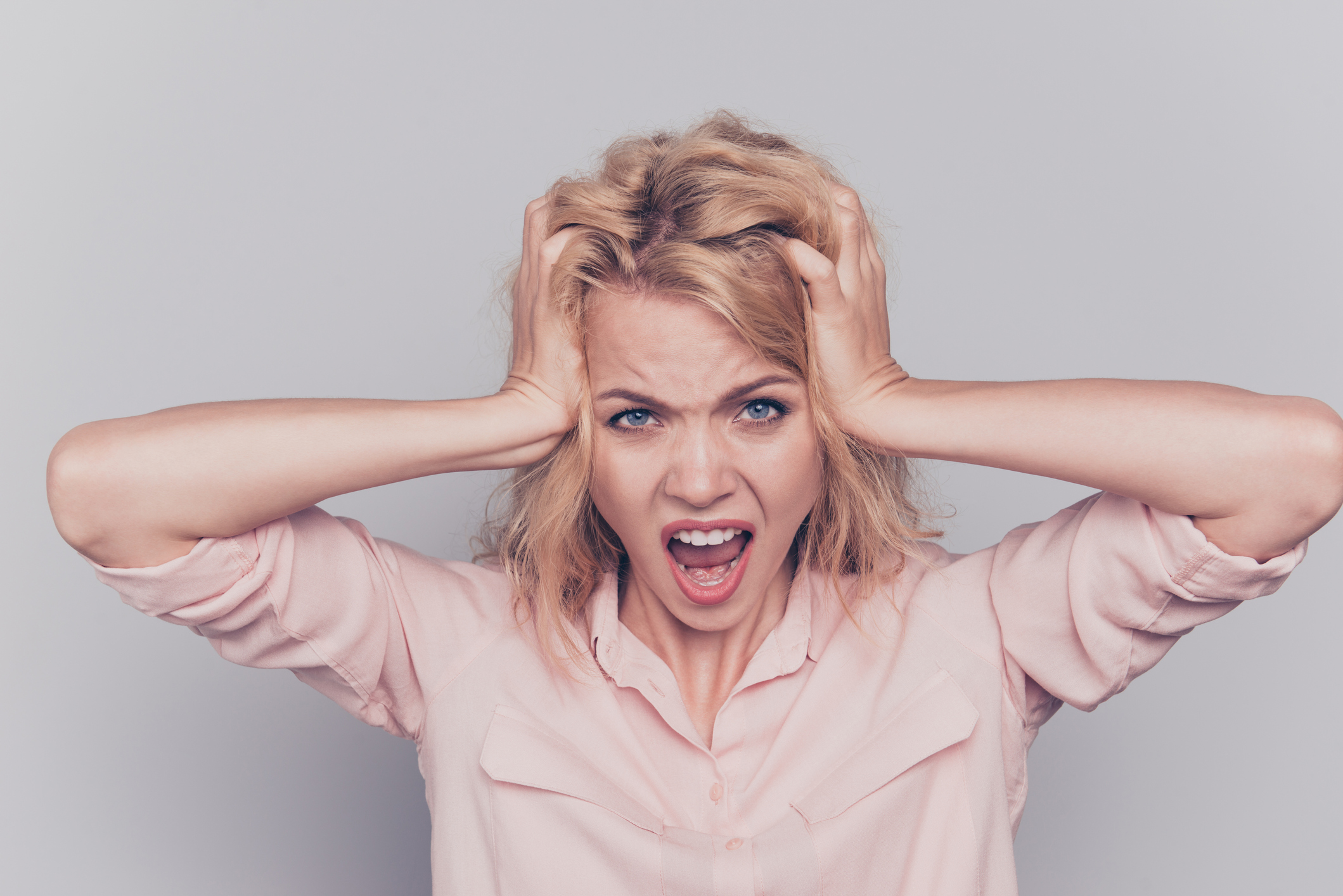 Woman holding her head with angry expression on her face.