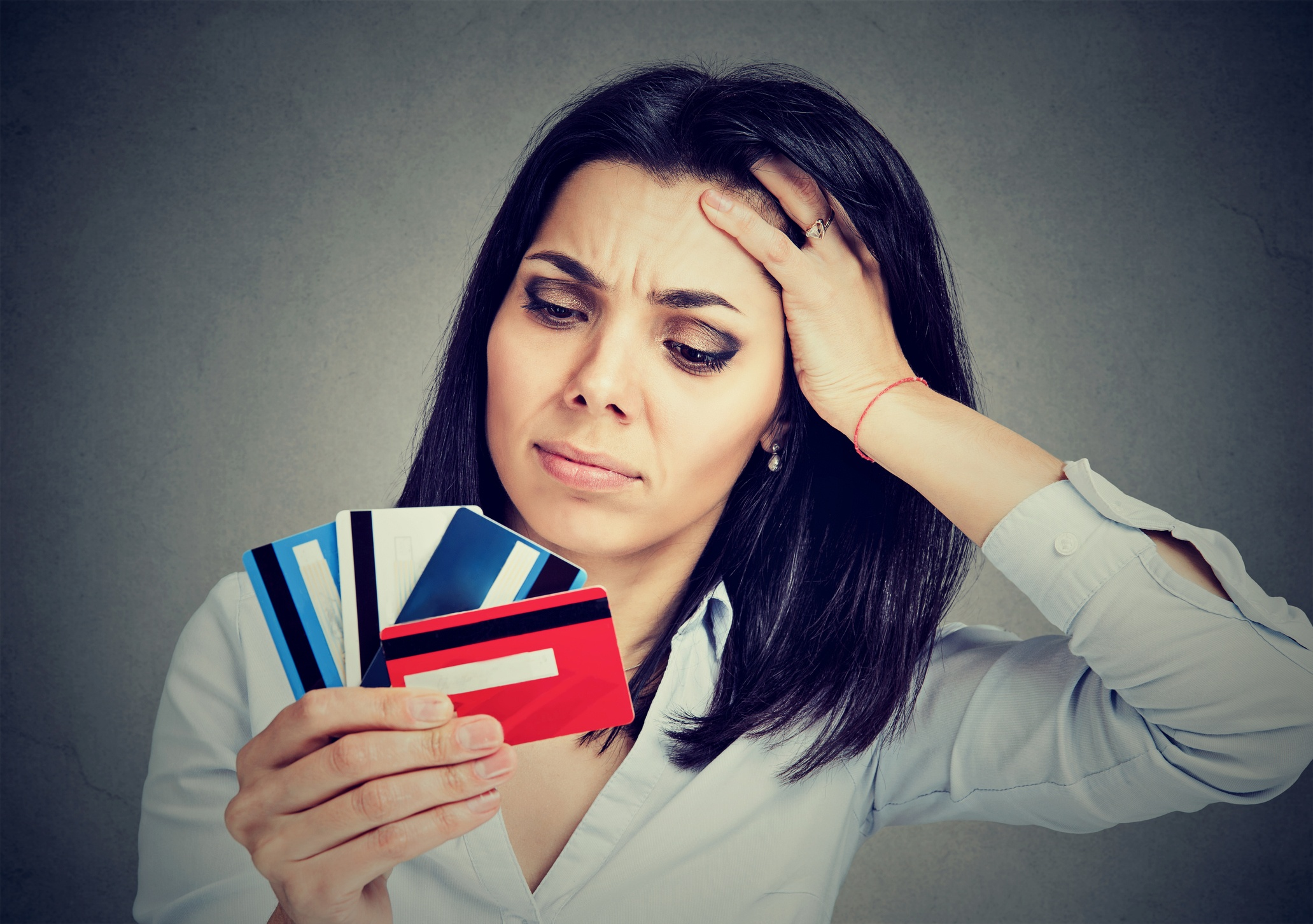 Woman looking at credit cards with confusion.