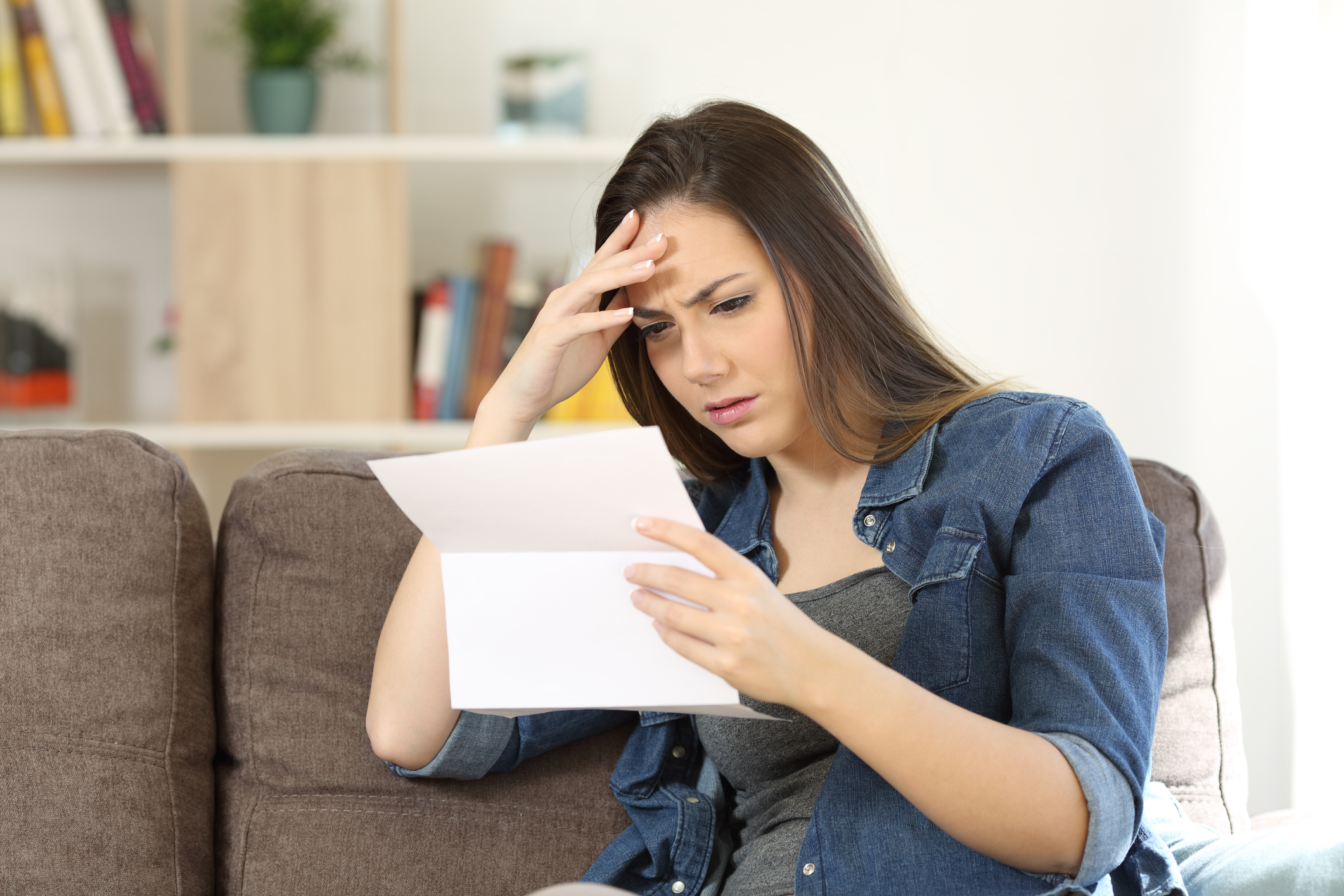 woman sitting on couch reading document while holding her head