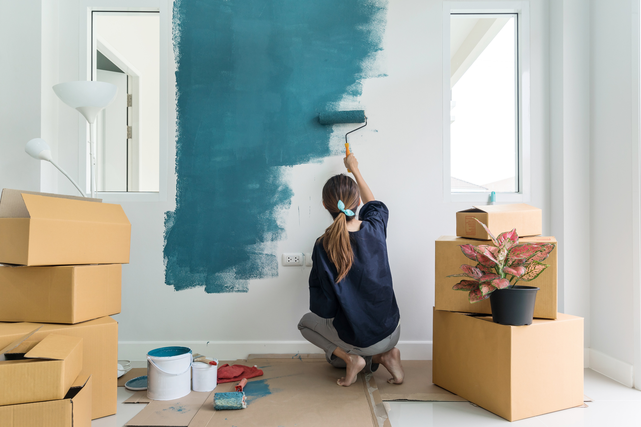 woman painting a wall in her home